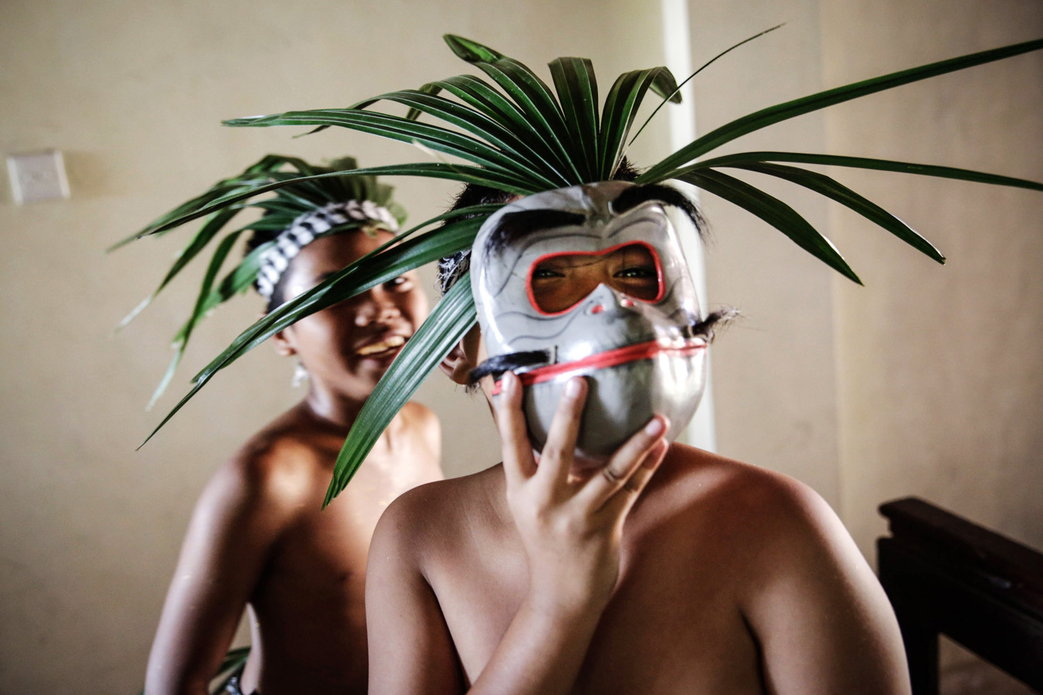 A boy plays with a monkey mask before taking part in a parade for the opening of the Bali International Arts Festival on June 13, 2014 in Denpasar, Indonesia.
