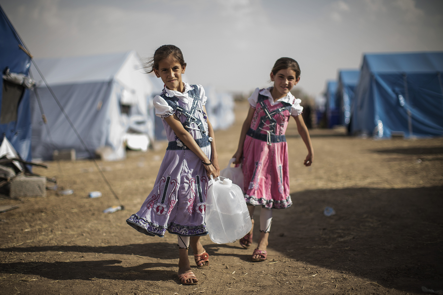 June 13, 2014. Iraqi children carry water to their tent at a temporary displacement camp set up next to a Kurdish checkpoint in Kalak.