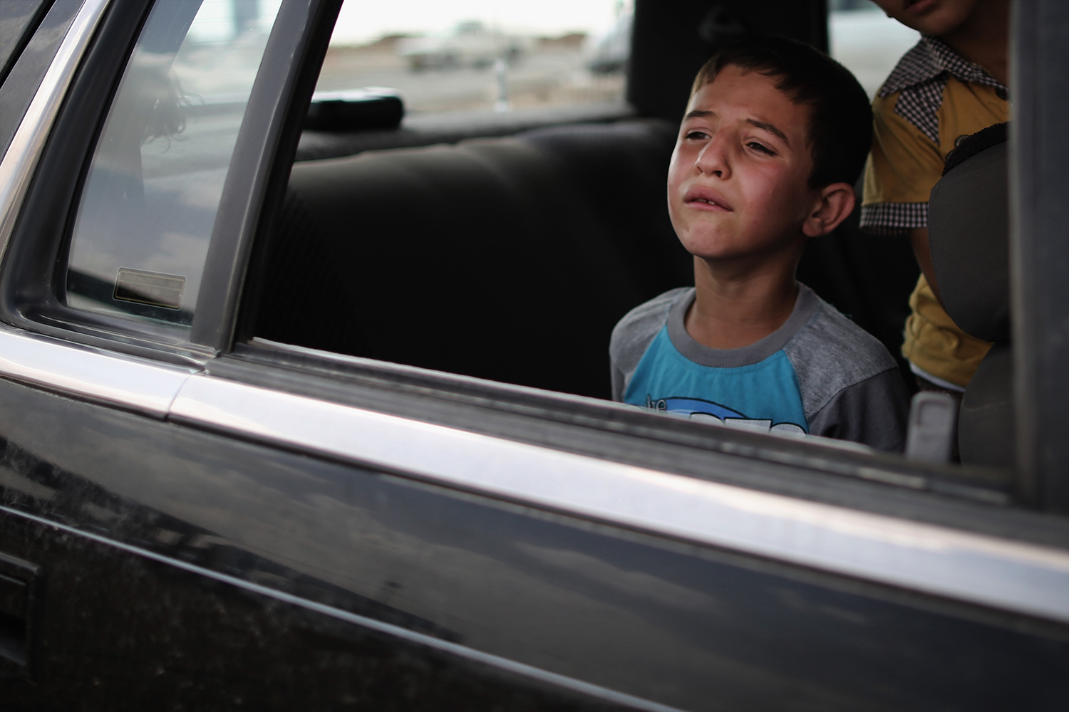 on June 13, 2014. A boy cries  while waiting in a car at a Kurdish checkpoint in Kalak, Iraq.