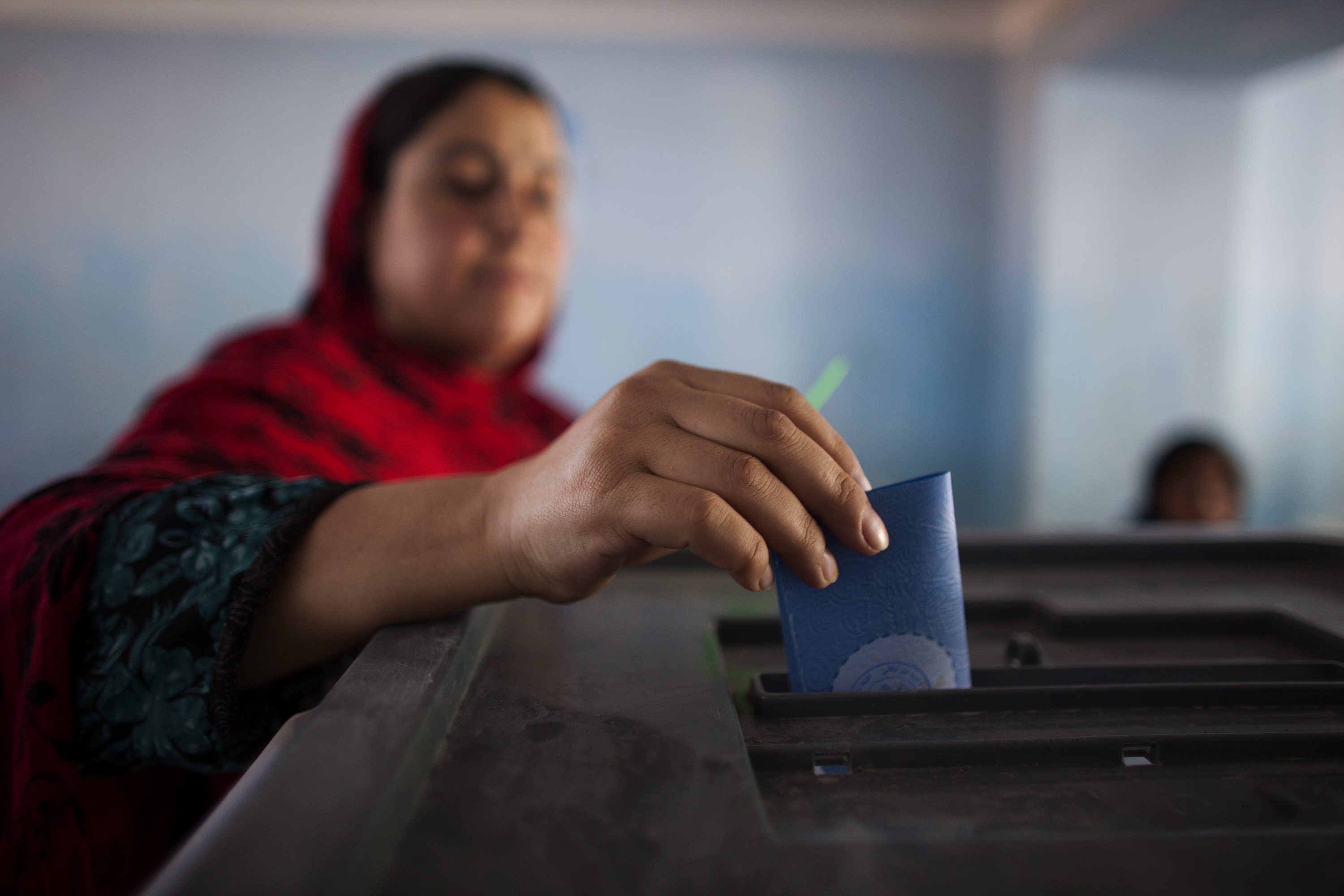 An Afghan woman casts her ballot during the second round for presidential election at a polling station in Kabul, Afghanistan, on June 14, 2014.