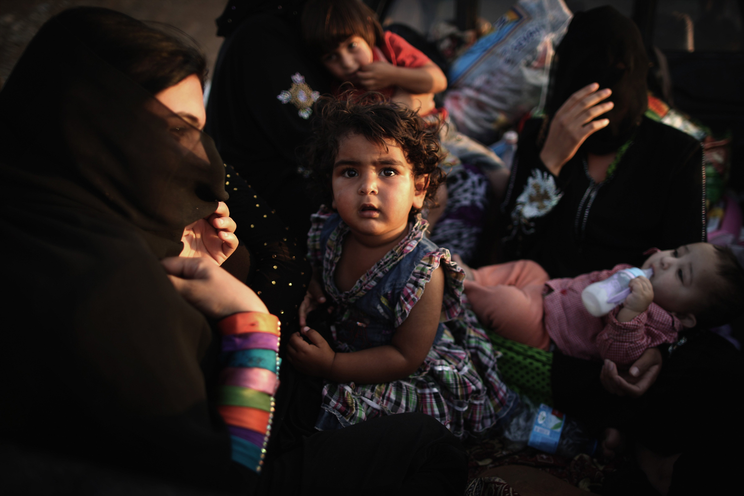 Jun. 14, 2014. Families arrive at a Kurdish checkpoint next to a temporary displacement camp in Kalak, Iraq.
