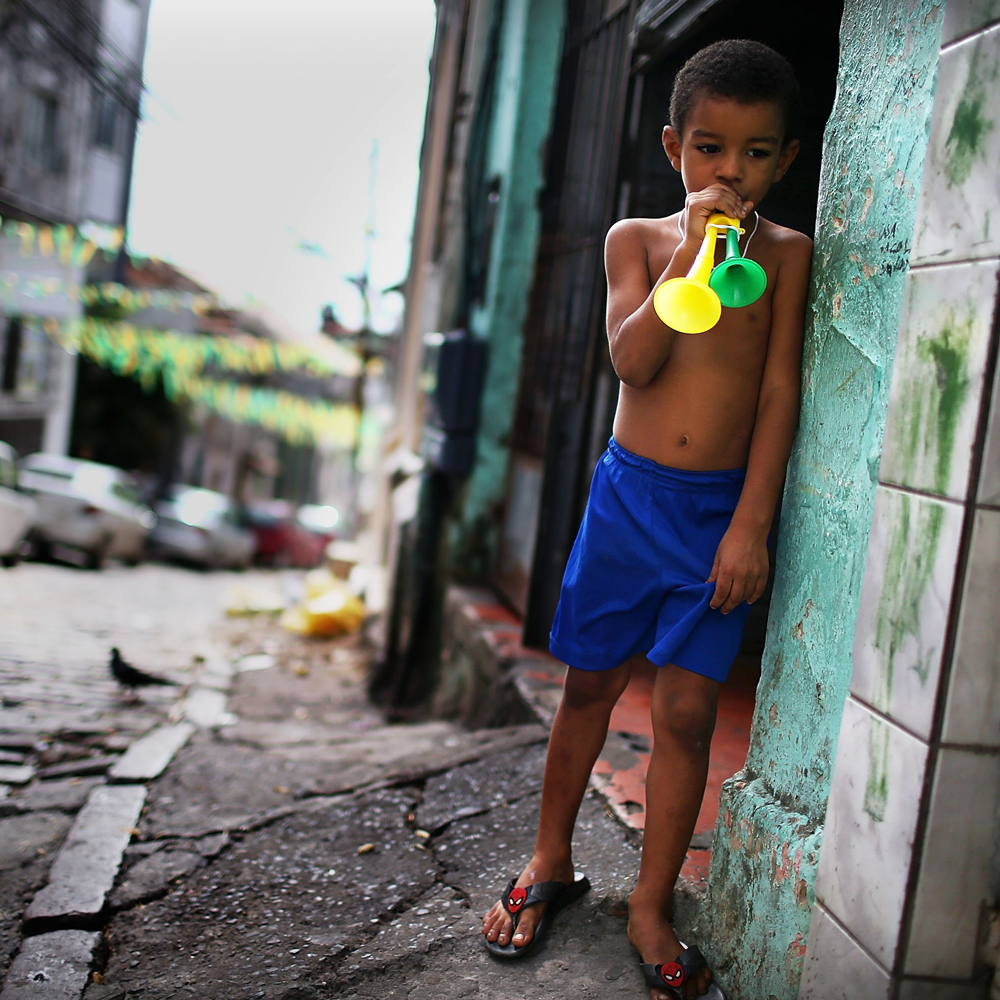 June 17, 2014. A young Brazil fan stands playing Brazil colored horns on the street prior to the Brazil-Mexico match in the 2014 FIFA World Cup  in Salvador, Brazil.