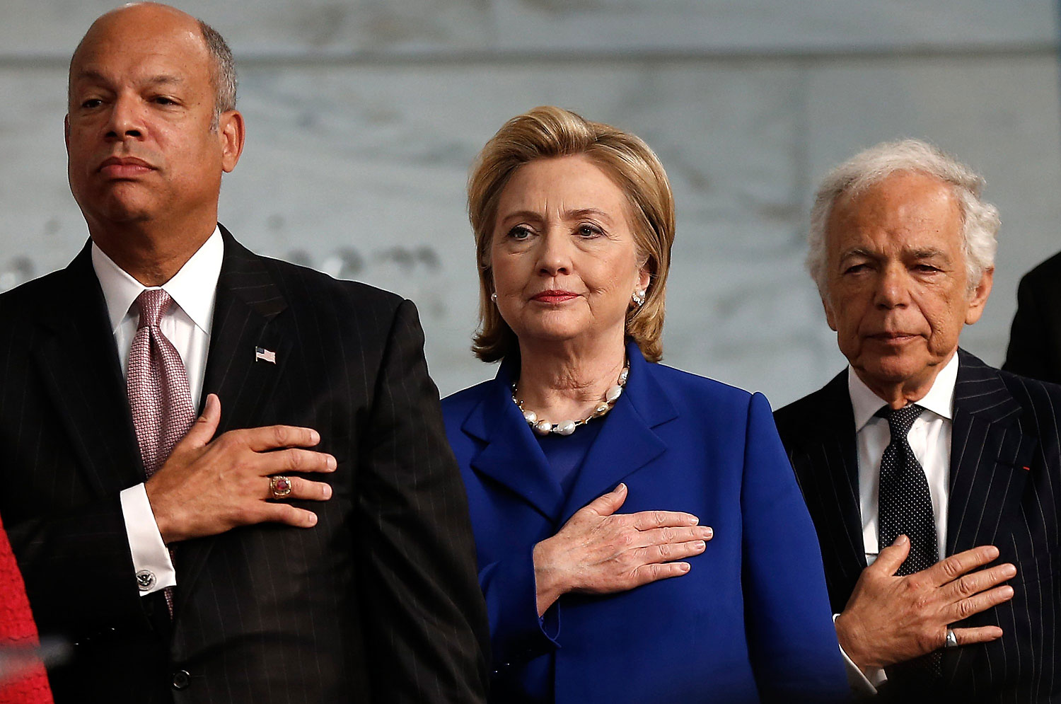 From left, U.S. Secretary of Homeland Security Jeh Johnson, Former U.S. Secretary of State Hillary Clinton and designer Ralph Lauren say the Pledge of Allegiance during a naturalization ceremony at the National Museum of American History June 17, 2014 in Washington, DC.
