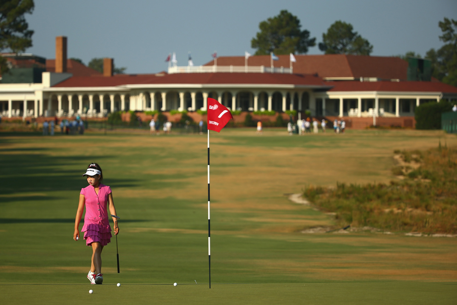 Jun. 18, 2014. Eleven-year old Amateur Lucy Li of the United States walks on the first green during a practice round prior to the start of the 69th U.S. Women's Open at Pinehurst Resort and Country Club in Pinehurst, North Carolina.
