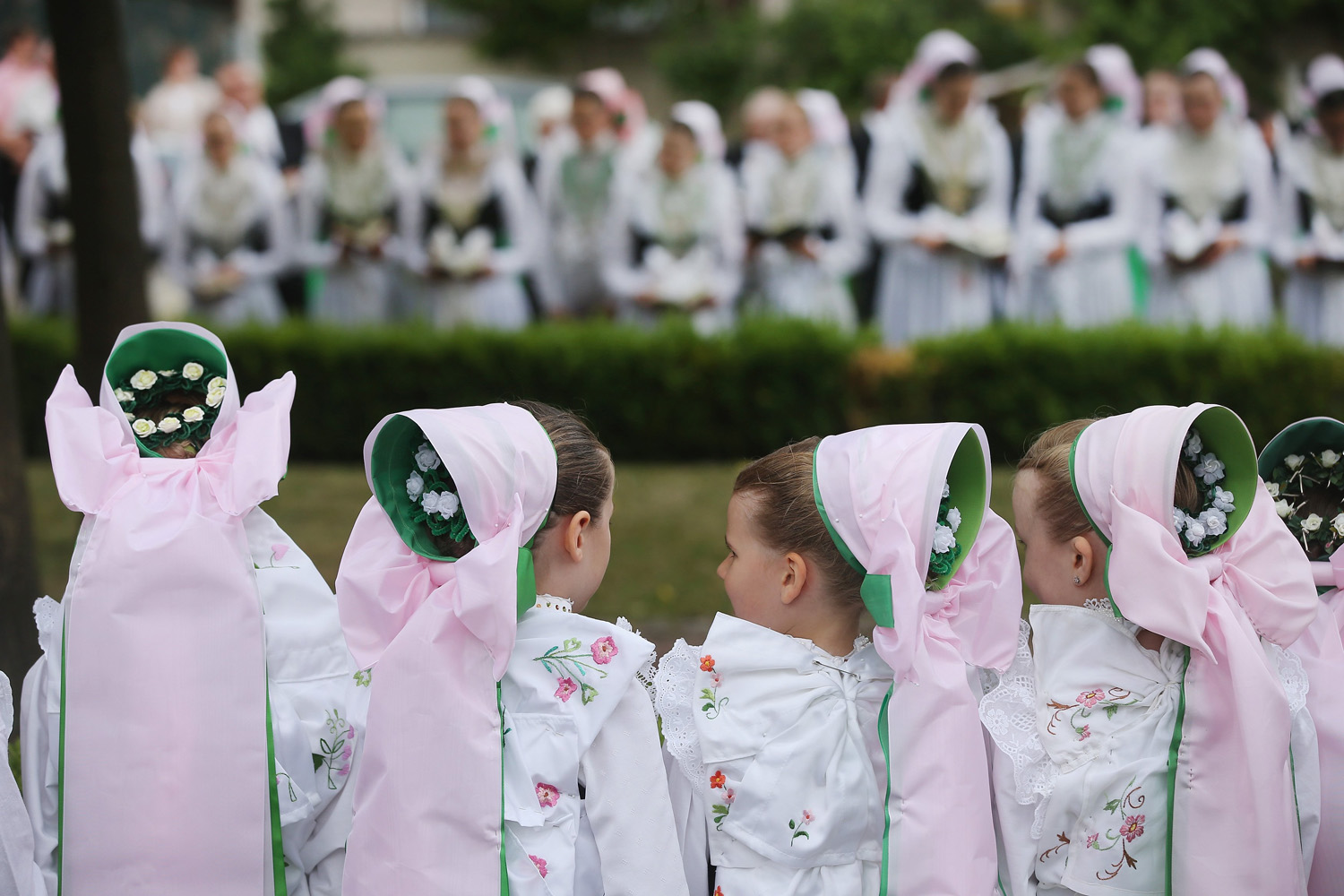 Jun. 19, 2014. Sorbian girls and young women in traditional Sorbian folk dress gather for an outdoor mass following a procession during Corpus Christi celebrations in Crostwitz, Germany.