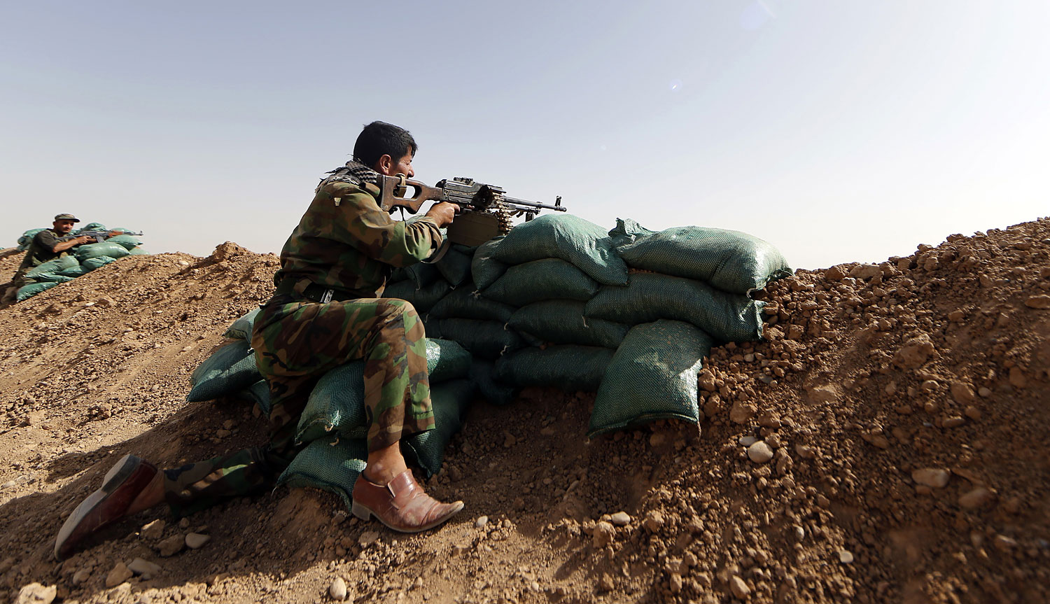 Members of Kurdish forces hold their position in the Iraqi village of Basheer on June 21, 2014