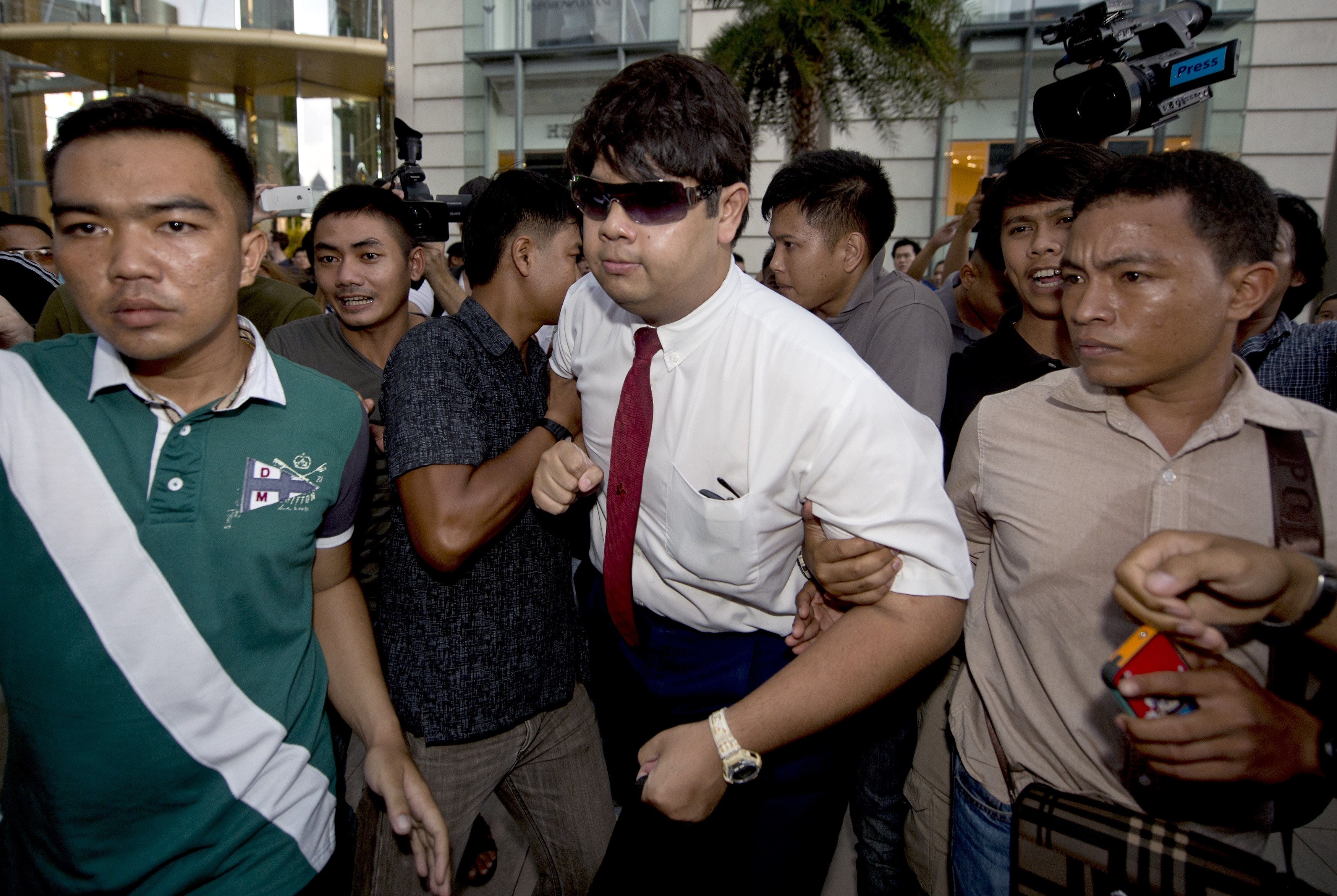 Thai policemen arrest a student for reading George Orwell's 1984 at a shopping mall in Bangkok on June 22, 2014