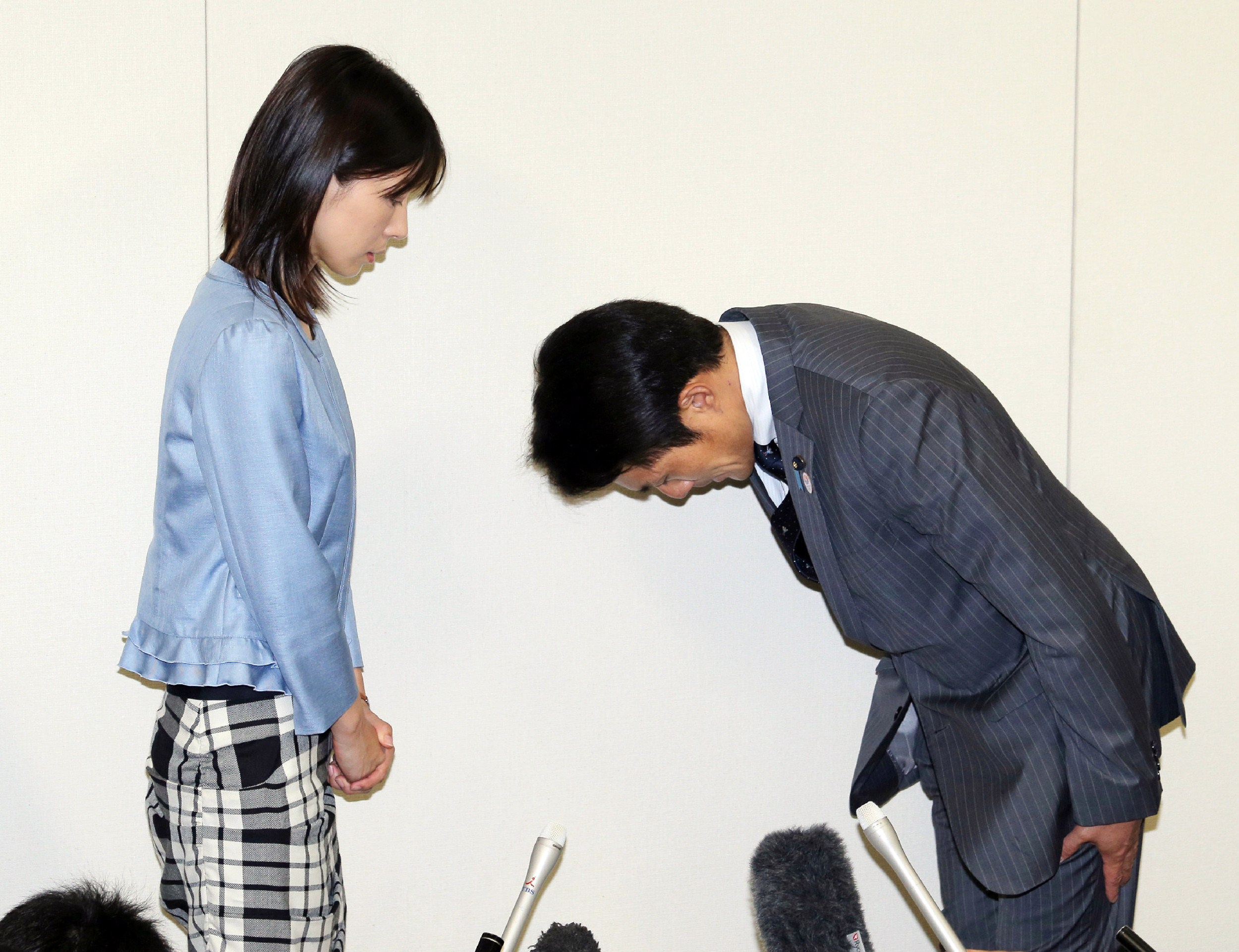 Akihiro Suzuki, a member of the Tokyo metropolitan assembly, bows to Ayaka Shiomura, a fellow assembly member, to apologize for his sexist jeer during a recent event, at Tokyo city hall on June 23, 2014.