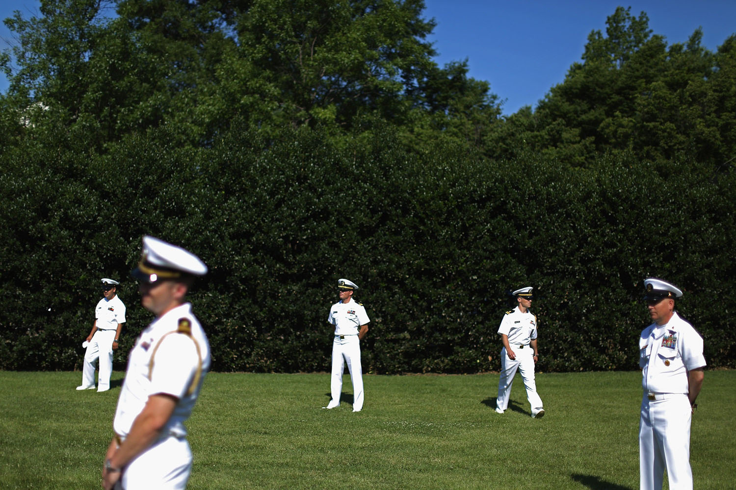 Jun. 23, 2014. U.S. Navy officers wait for the start of an award ceremony to honor the victims and recognize the heroic actions of the people involved in the Washington Navy Yard shootings at Luetze Park at the military base in Washington, DC.