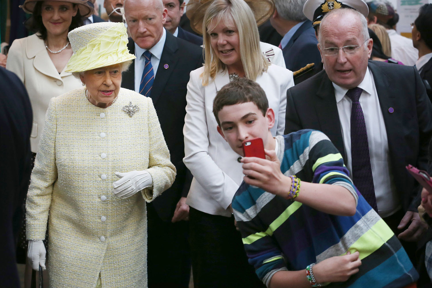 Jun. 24, 2014. A local youth takes a selfie photograph in front of Queen Elizabeth II during a visit to St George's indoor market in Belfast, Northern Ireland. The Royal party are visiting Northern Ireland for three days.