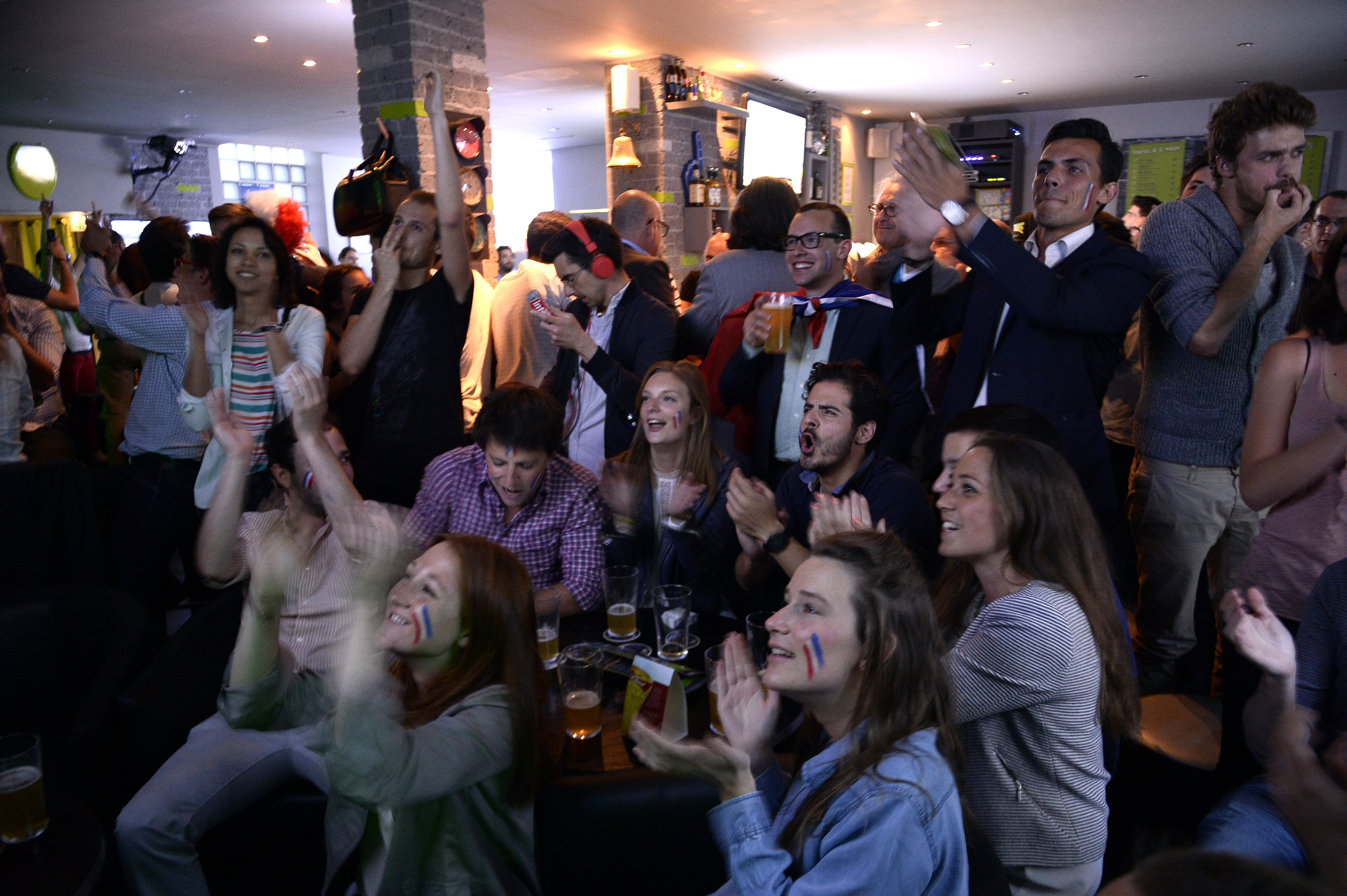Football fans react during the FIFA World Cup 2014 football match between France and Ecuador on June 25, 2014 at a bar in Paris.