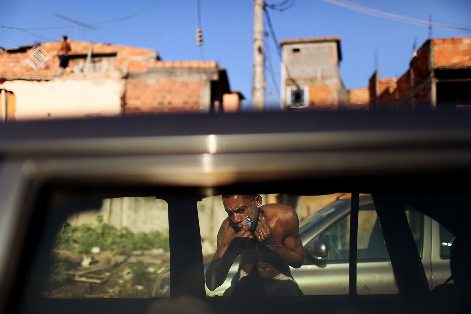 June 25, 2014. A resident shaves using a car window as a mirror amongst cars parked by World Cup tourists for a fee in the Metro Mangueira favela, located 750 meters from Maracana stadium, in Rio de Janeiro, Brazil.