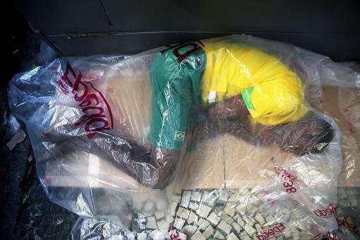 Jun. 25, 2014.  A man sleeps on a sidewalk in Copacabana while dressed in Brazil colors in Rio de Janeiro, Brazil.