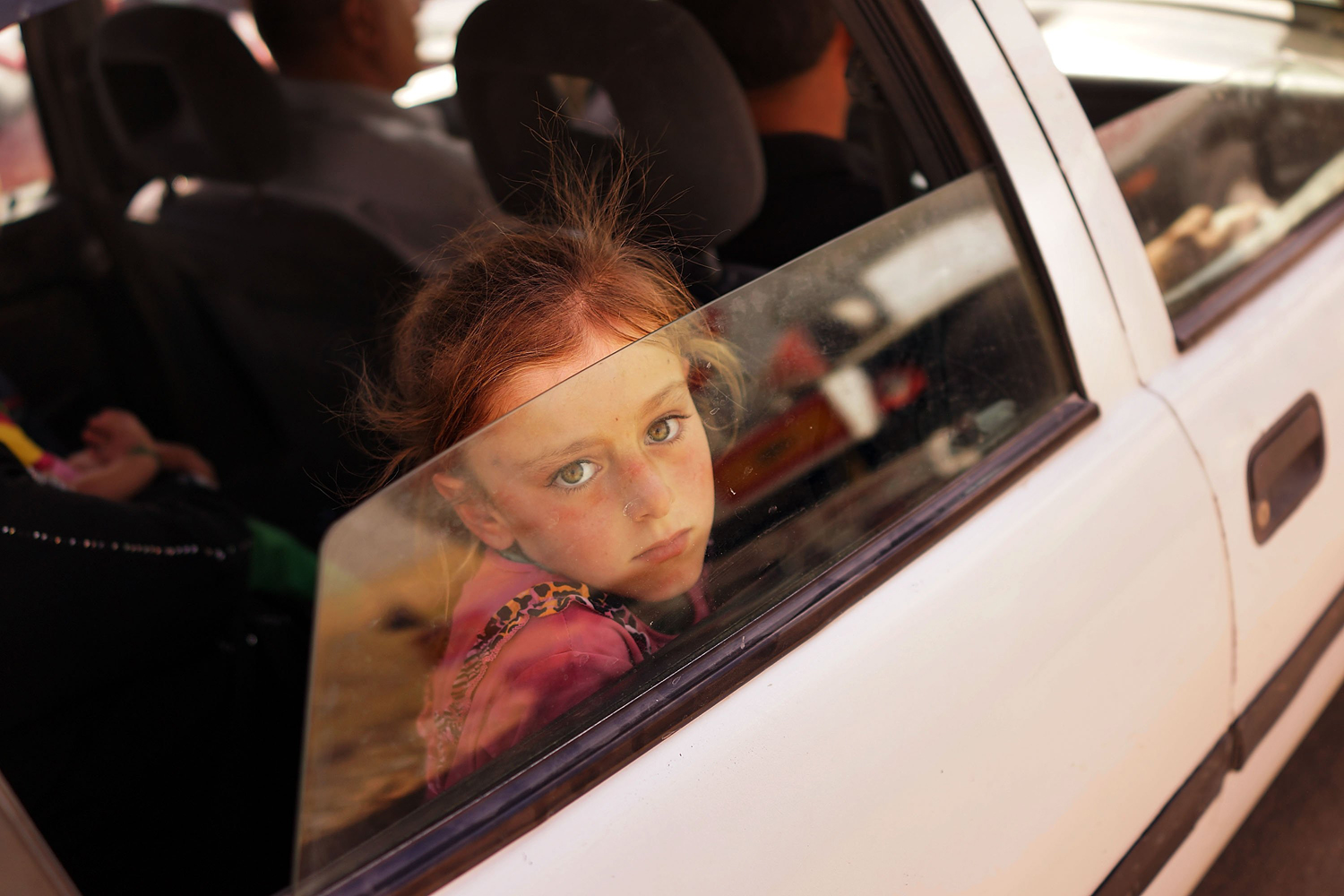 Jun. 26, 2014. An Iraqi child looks out of the window of her car as she waits to get into a temporary displacement camp for Iraqis caught-up in the fighting in and around the city of Mosul in Khazair, Iraq.