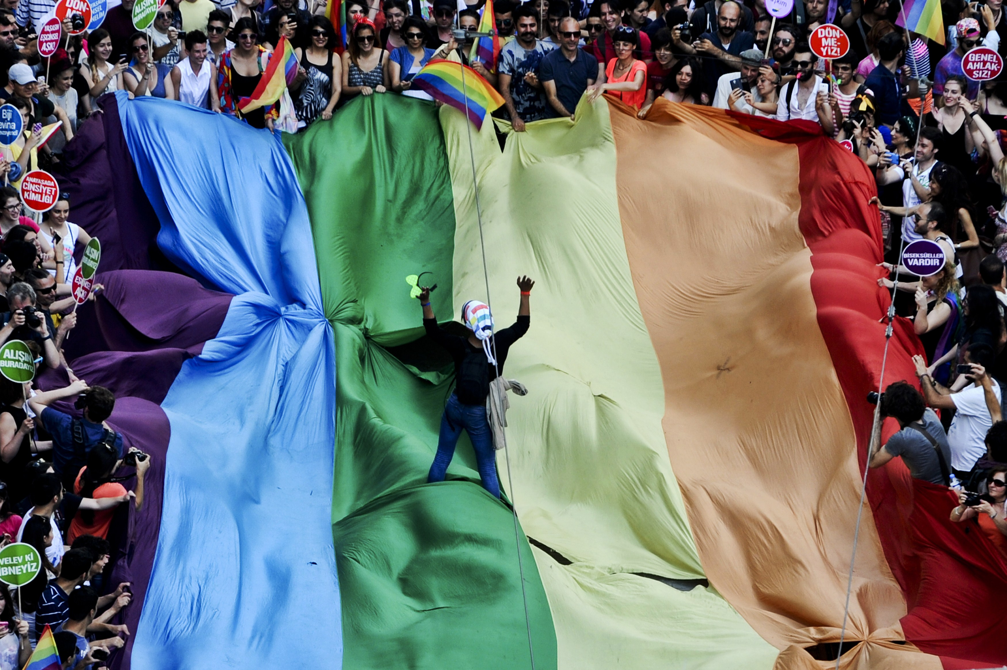 People march holding a giant rainbow flag during a gay pride parade on Istiklal Street, in Istanbul, Turkey, on June 29, 2014.