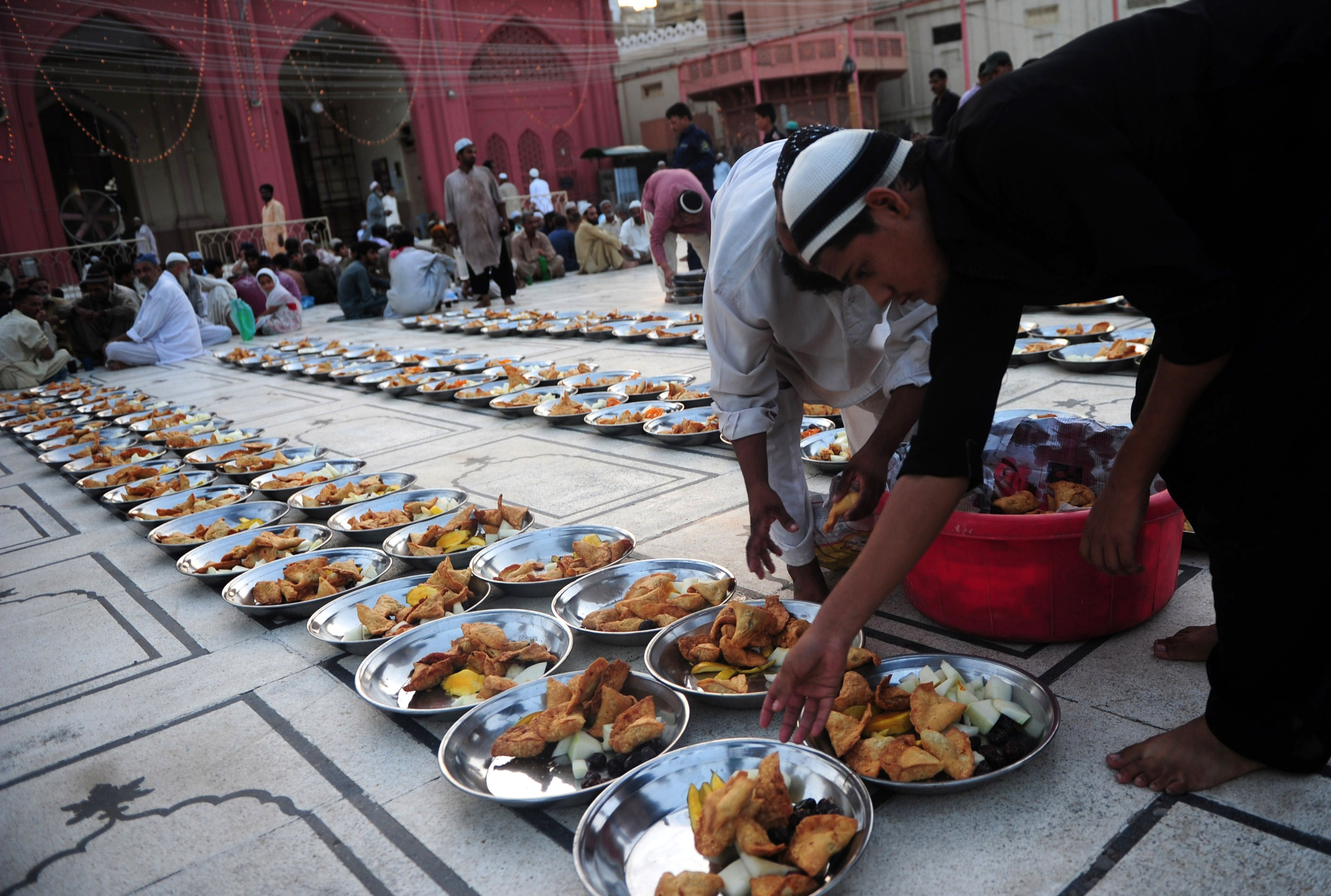 A Pakistani Muslim man arranges Iftar food for Muslim devotees before they break their fast during the holy fasting month of Ramadan in Karachi on June 30, 2014.