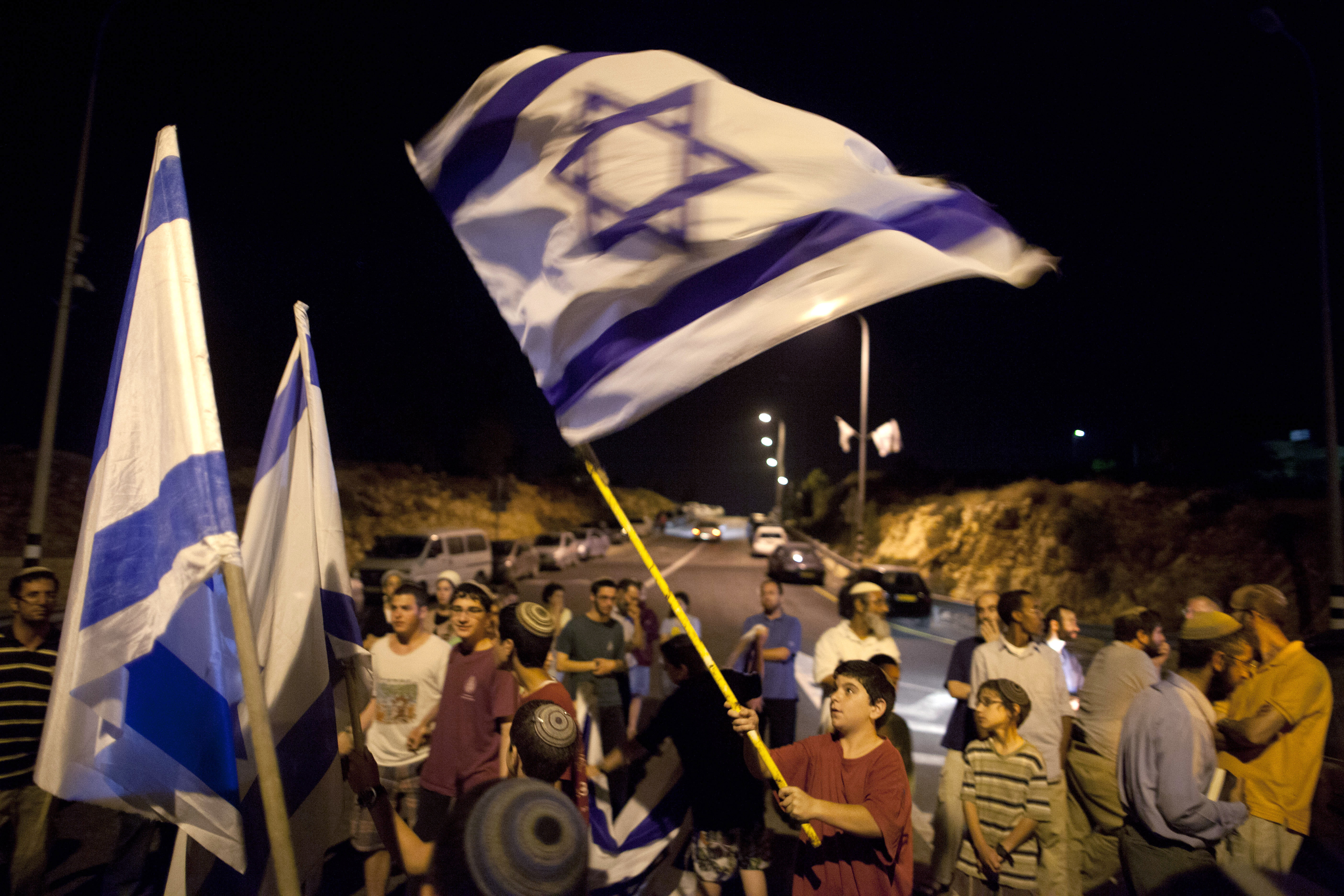 Israeli settlers hold flags on June 30, 2014, at the entrance to Halhoul, north of Hebron, West Bank