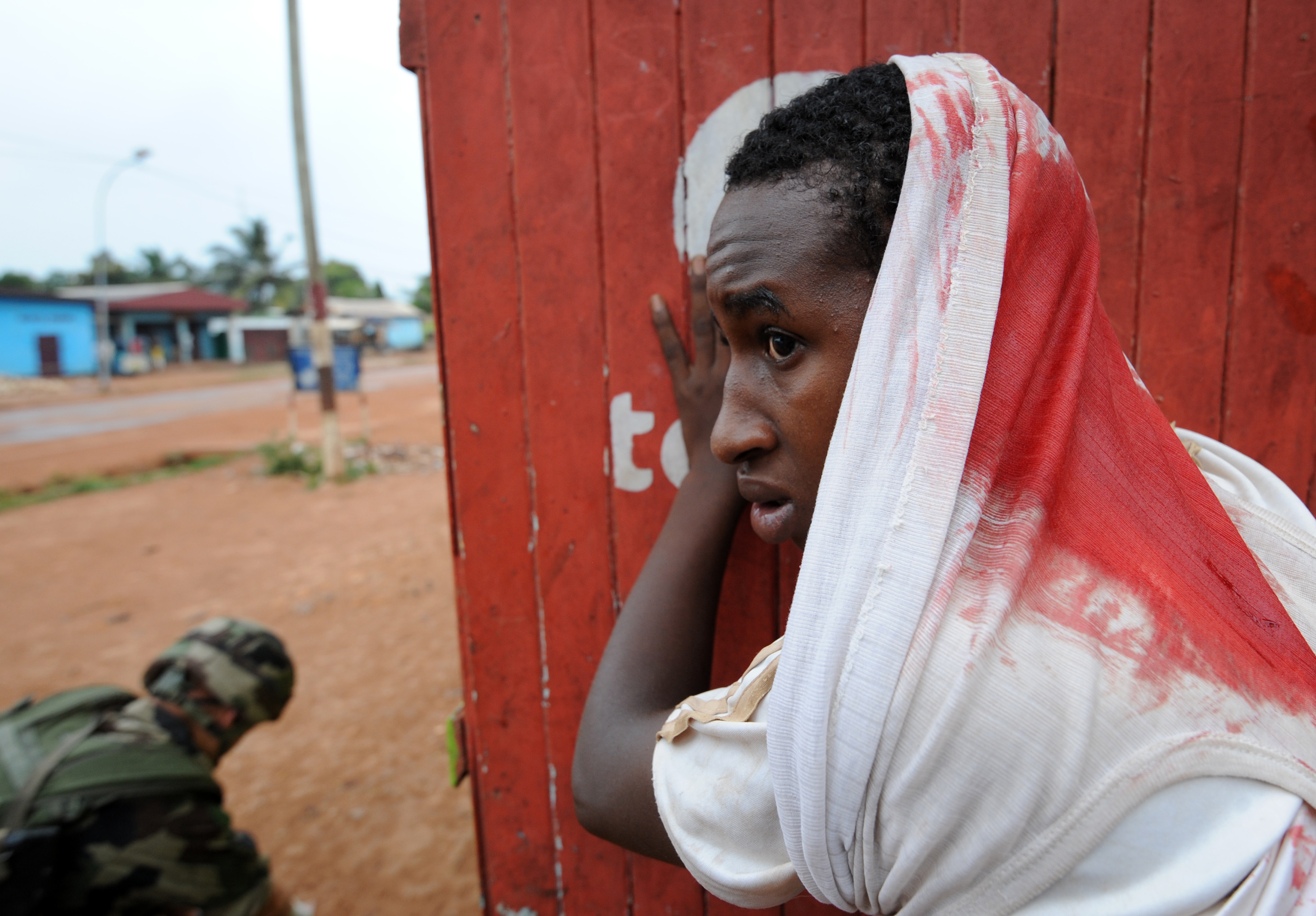 A wounded man waits for assistance during a disarmament operation by French soldiers in Bangui, on December 9, 2013.