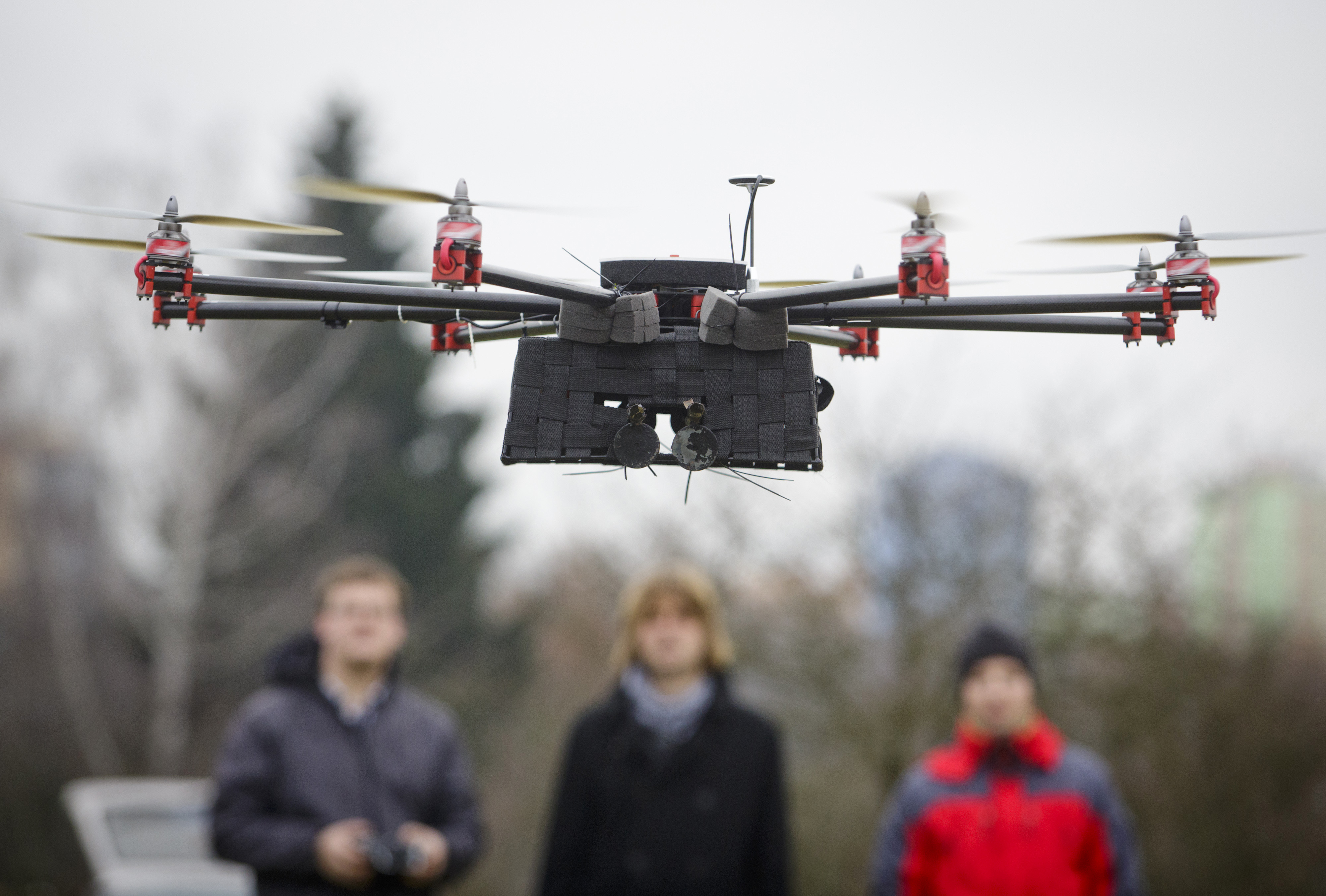 Technicians look on as a SteadiDrone EI8GHT Octocopter hovers during a test flight in a field outside the headquarters of Mensuro Ltd., a distributor for SteadiDrone Ltd. products, in Pilsen, Czech Republic, on Tuesday, Dec. 10, 2013.