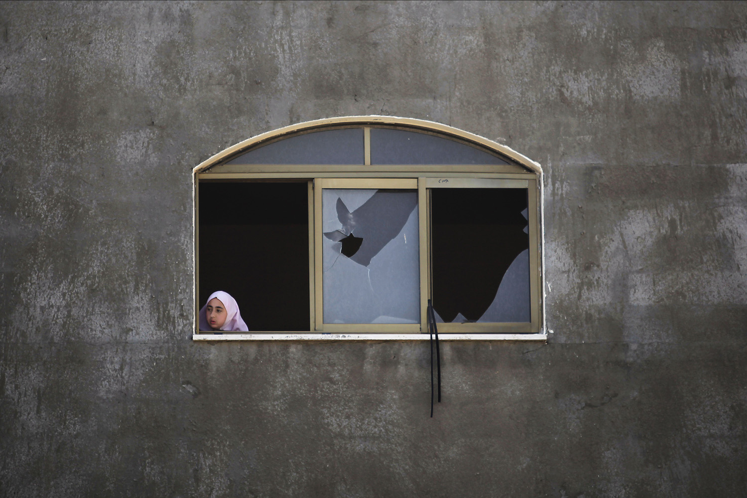 June 16, 2014. A Palestinian girl looks at a damaged home after it was hit by an Israeli missile strike in Gaza City.