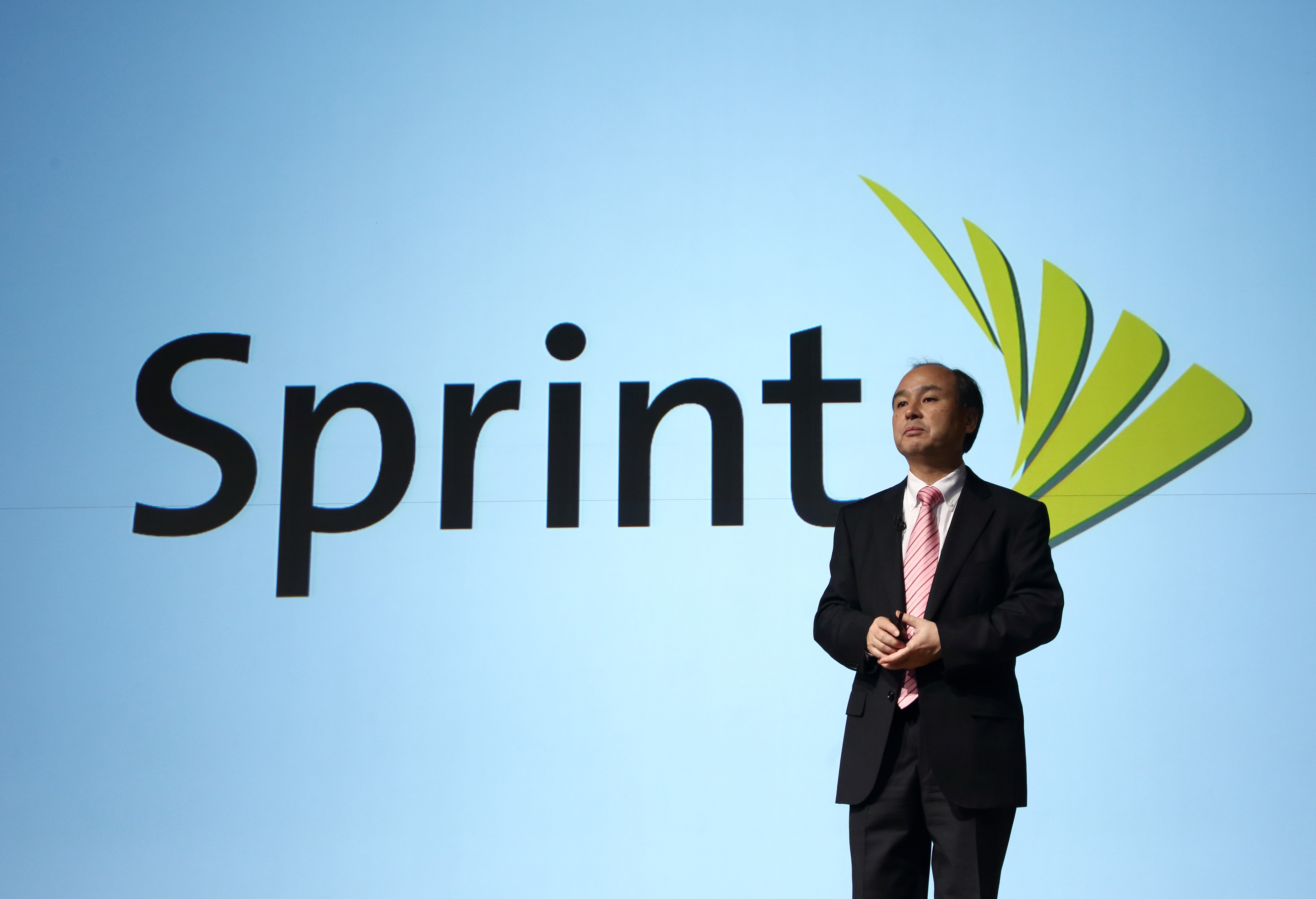 Billionaire Masayoshi Son, chairman and chief executive officer of SoftBank Corp., speaks in front of a screen displaying the logo of Sprint Corp. during a news conference in Tokyo, Japan, on Wednesday, Feb. 12, 2014.