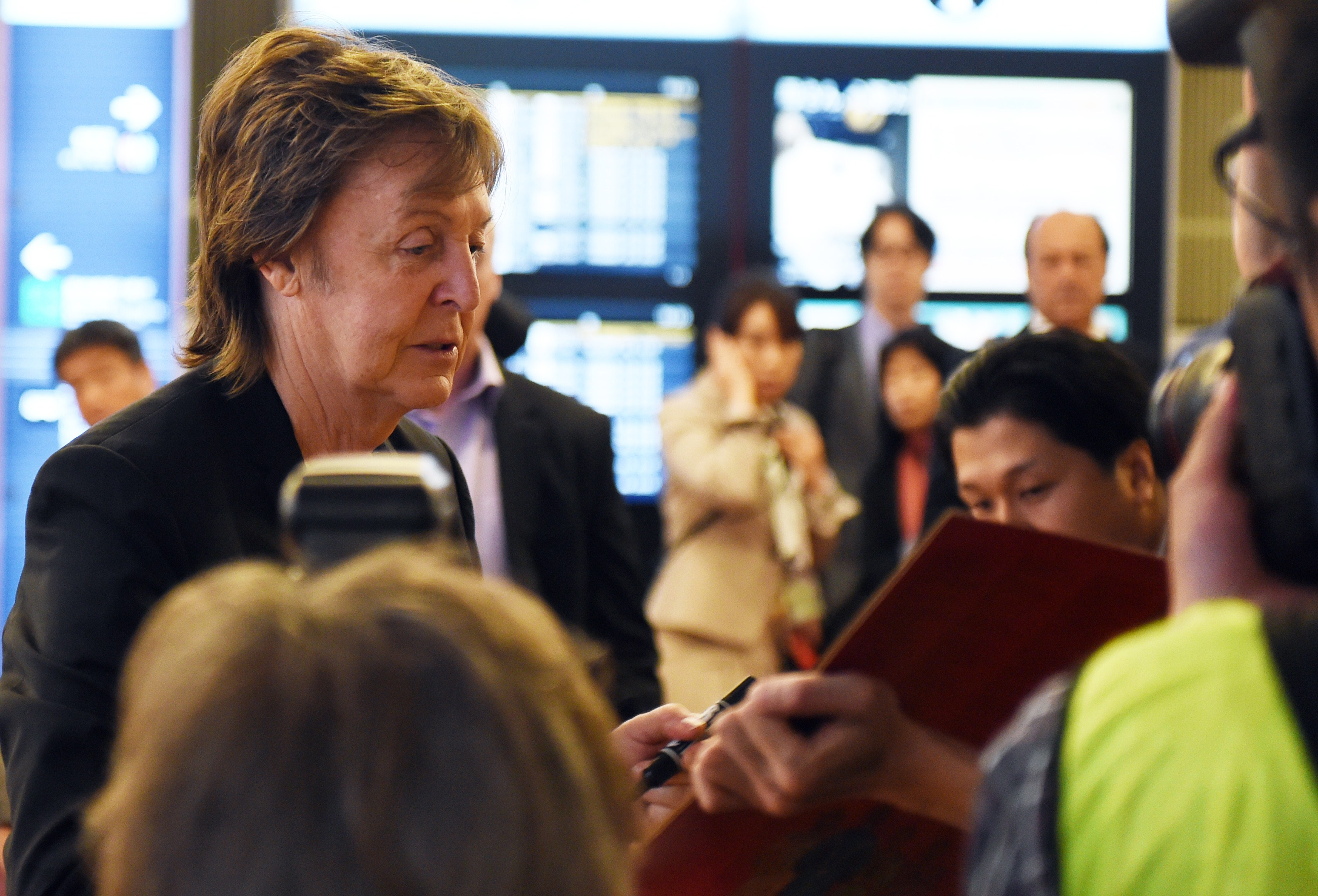 Paul McCartney (L) signs his autograph upon his arrival at the Haneda airport in Tokyo on May 15, 2014.