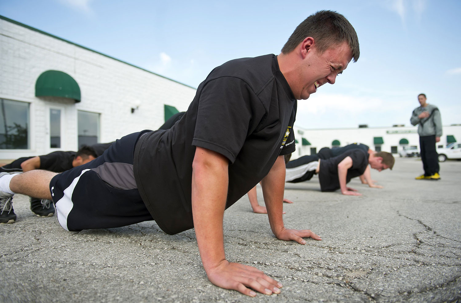 Kyle Bayard, 20, struggles to remain in position during a stationary push-up during physical exercise in the parking lot behind the Army recruiting station in Grandview, Mo., May 6, 2014.