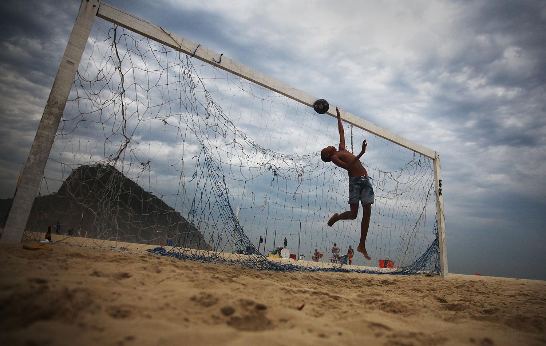 A boy practices defending penalty kicks with friends on Copacabana Beach in Rio de Janeiro on June 1, 2014 .