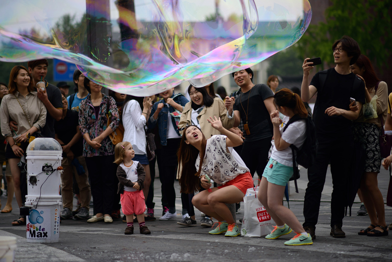 Tourists react to a large bubble created by a street performer in Seoul on June 2, 2014.