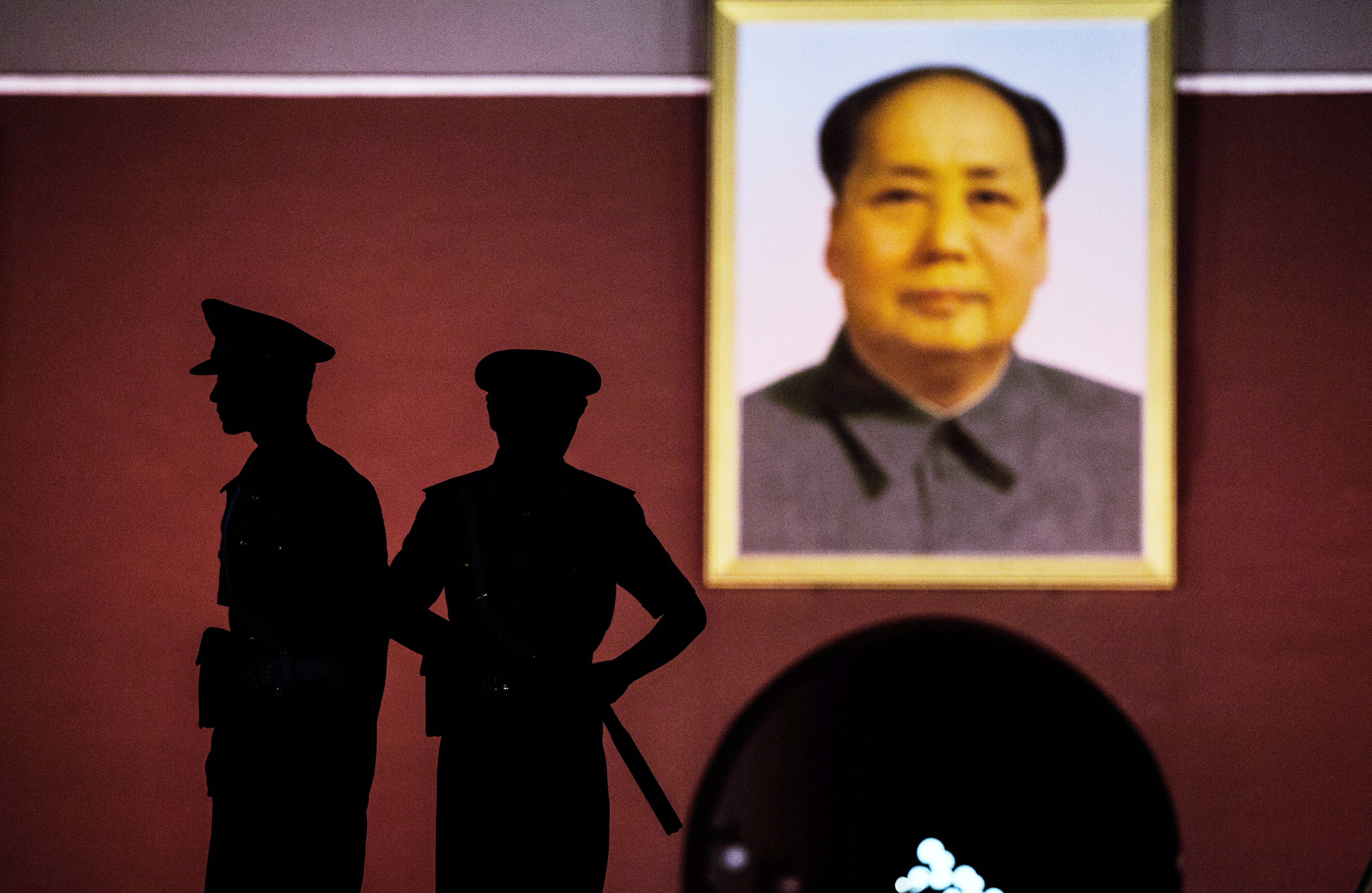 Chinese Paramilitary security force officers stand under a portrait of the late Mao Zedong outside the Forbidden City at Tiananmen Square on June 2, 2014 in Beijing, China.