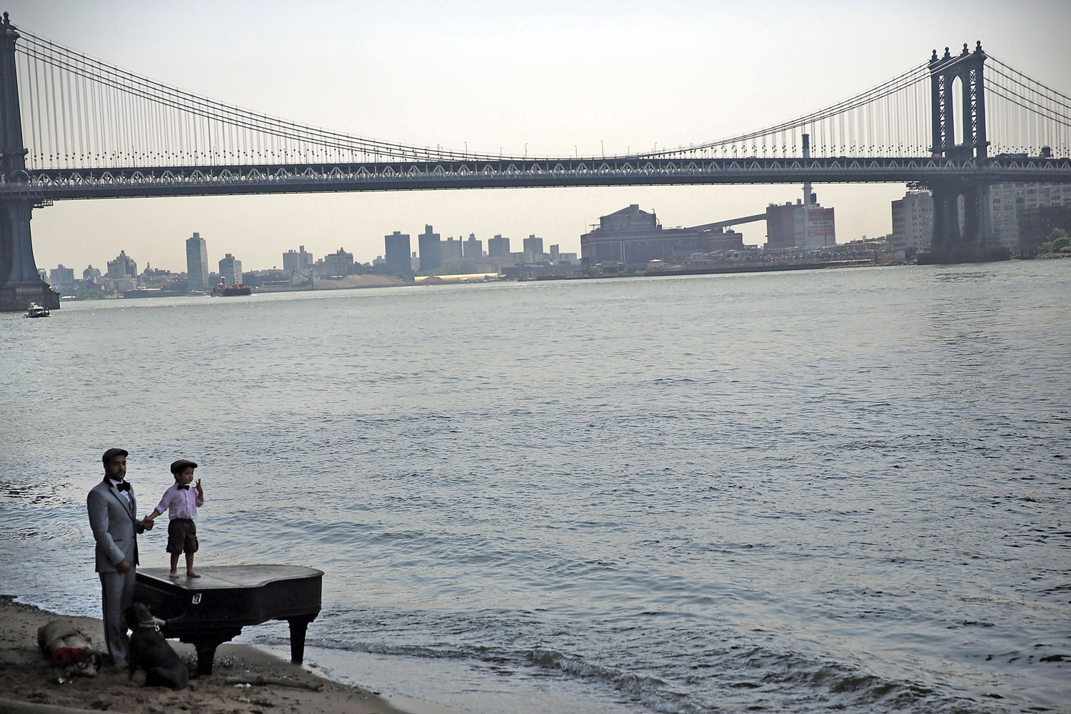 Mark Deliz and his son Sebastion, 3, pause at a grand piano that has mysteriously landed on a sliver of beach underneath the Brooklyn Bridge in New York City on June 3, 2014.