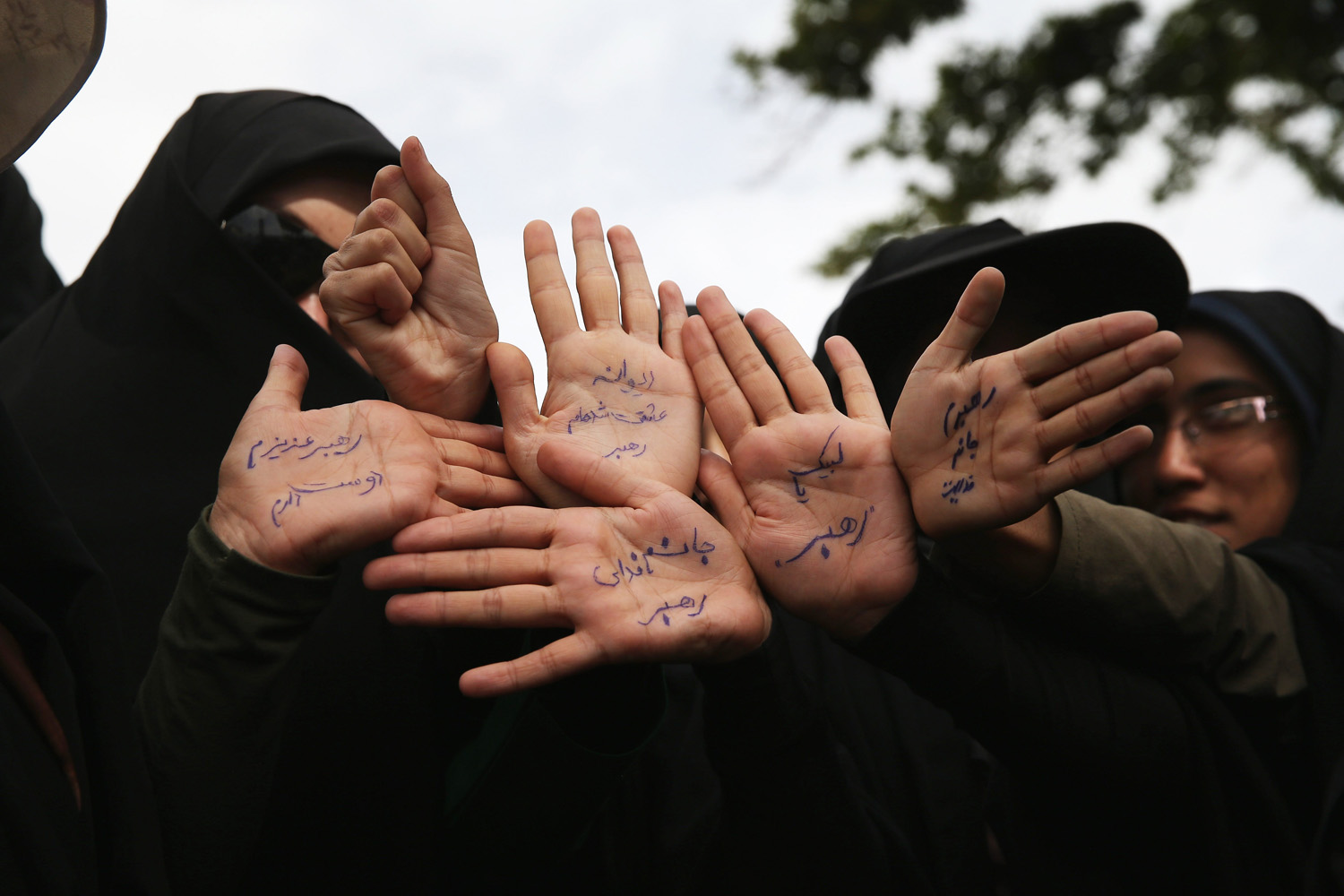 June 4, 2014. Women hold up their hands pledging to offer their lives, if needed, for the Islamic Revolution outside the shrine of the Ayatollah Khomeini on the 25th anniversary of his death on the outskirts of Tehran, Iran.