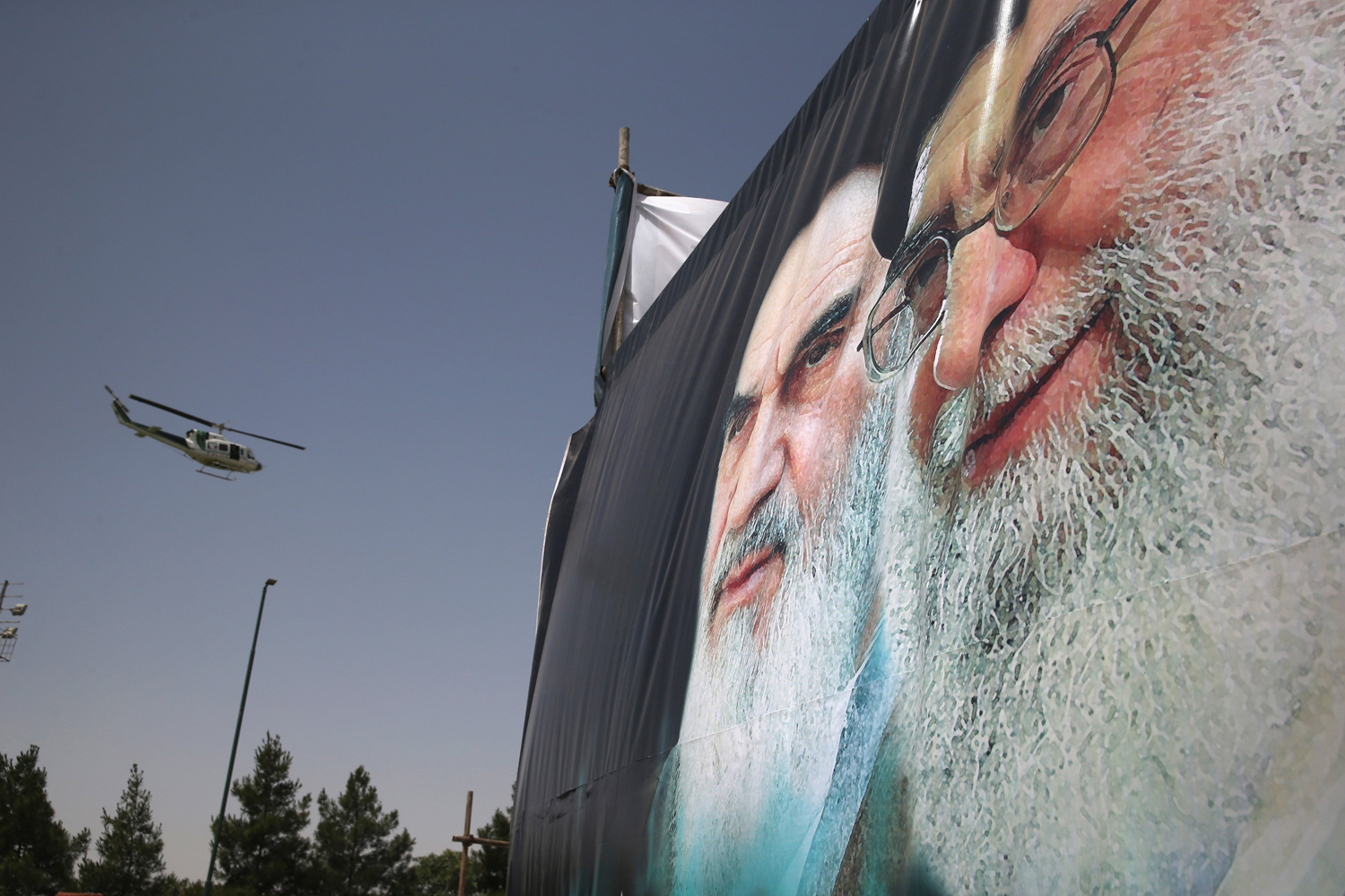 June 4, 2014.  An Iranian police helicopter passes above portraits of Iran's supreme leader Ayatollah Ali Khamenei (R) and the former Ayatollah Khomeini outside Khomeini's shrine on the 25th anniversary of his death on on the outskirts of Tehran, Iran.