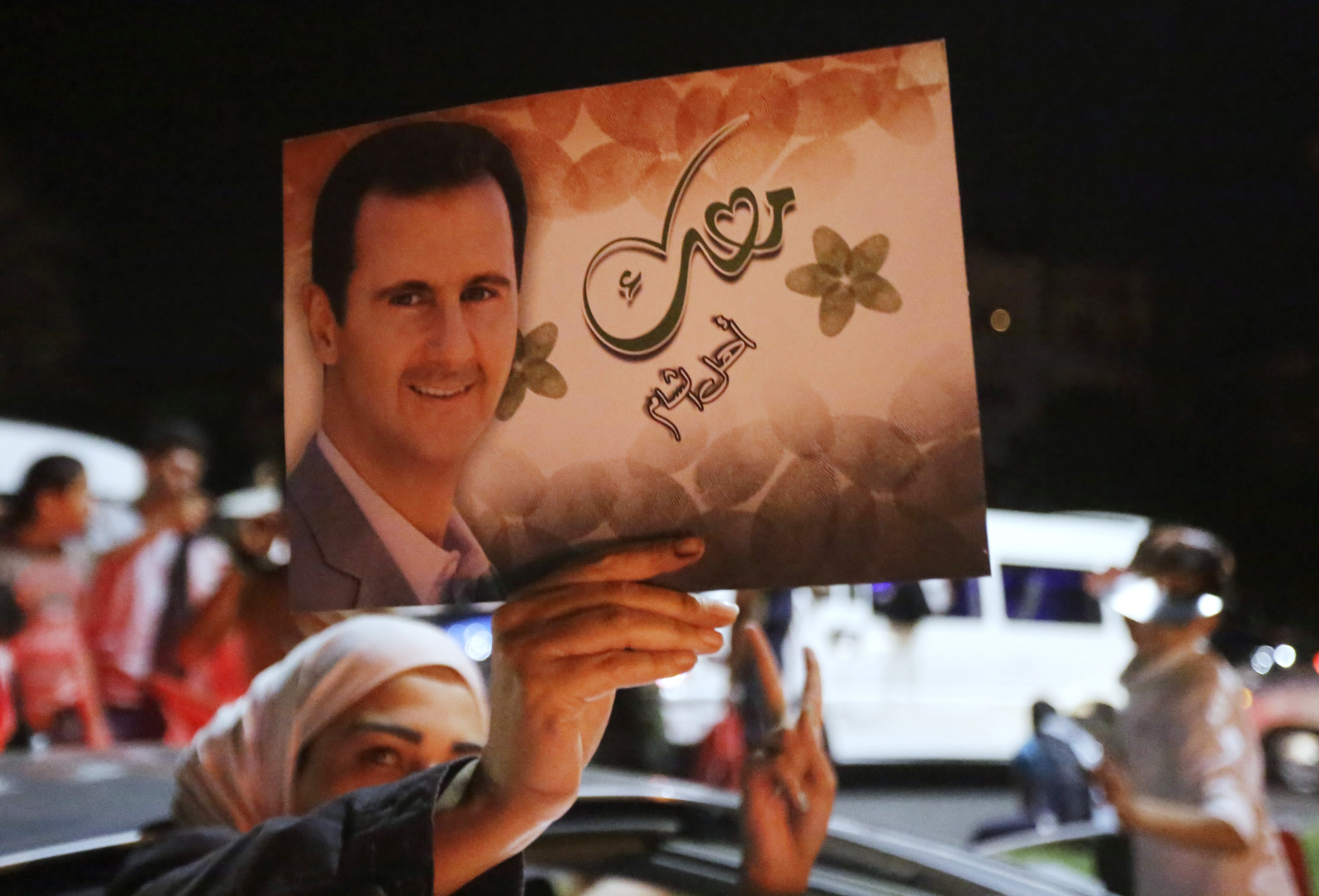 A woman holds a picture of re-elected Syrian President Bashar Assad as she celebrates in Damascus after he was announced as the winner of the presidential election on June 4, 2014.