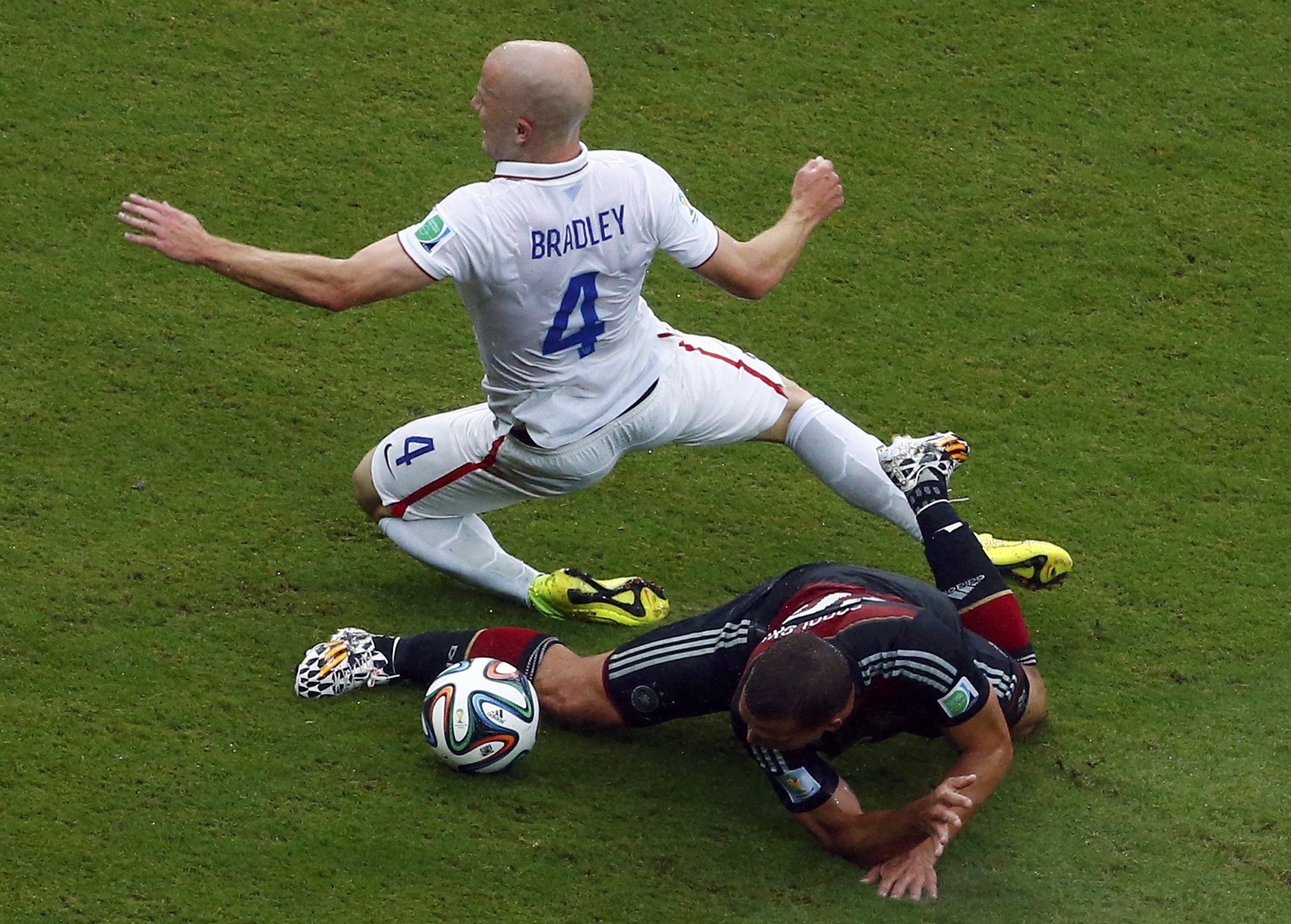 Michael Bradley of the U.S. falls over Germany's Lukas Podolski during their 2014 World Cup Group G soccer match at the Pernambuco arena in Recife, Brazil on June 26, 2014.