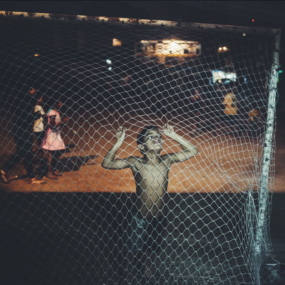 June 12, 2014. A boy who lives in the Moinho slum plays while residents watch the opening game of the FIFA World Cup. Sao Paulo.