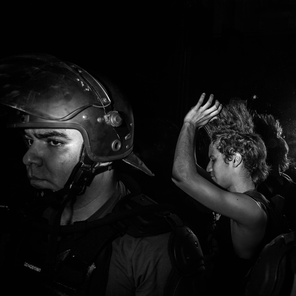 June 23, 2014. While the game Brazil vs Cameroon happened, a protest against the World Cup took place in the center of Sao Paulo. In the photograph a young demonstrator straighten his punk hair while he was in custody of the police after he was arrested during the protest.
