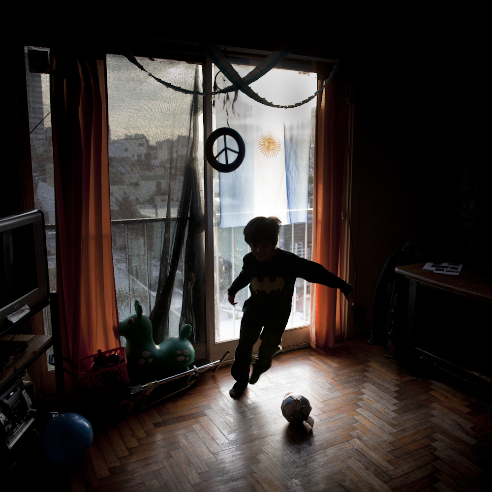 June 24, 2014. A boy plays football at home in his small apartment, with Argentina's flag behind hanging from the balcony. Lots of flags were hung in houses and apartments in Buenos Aires