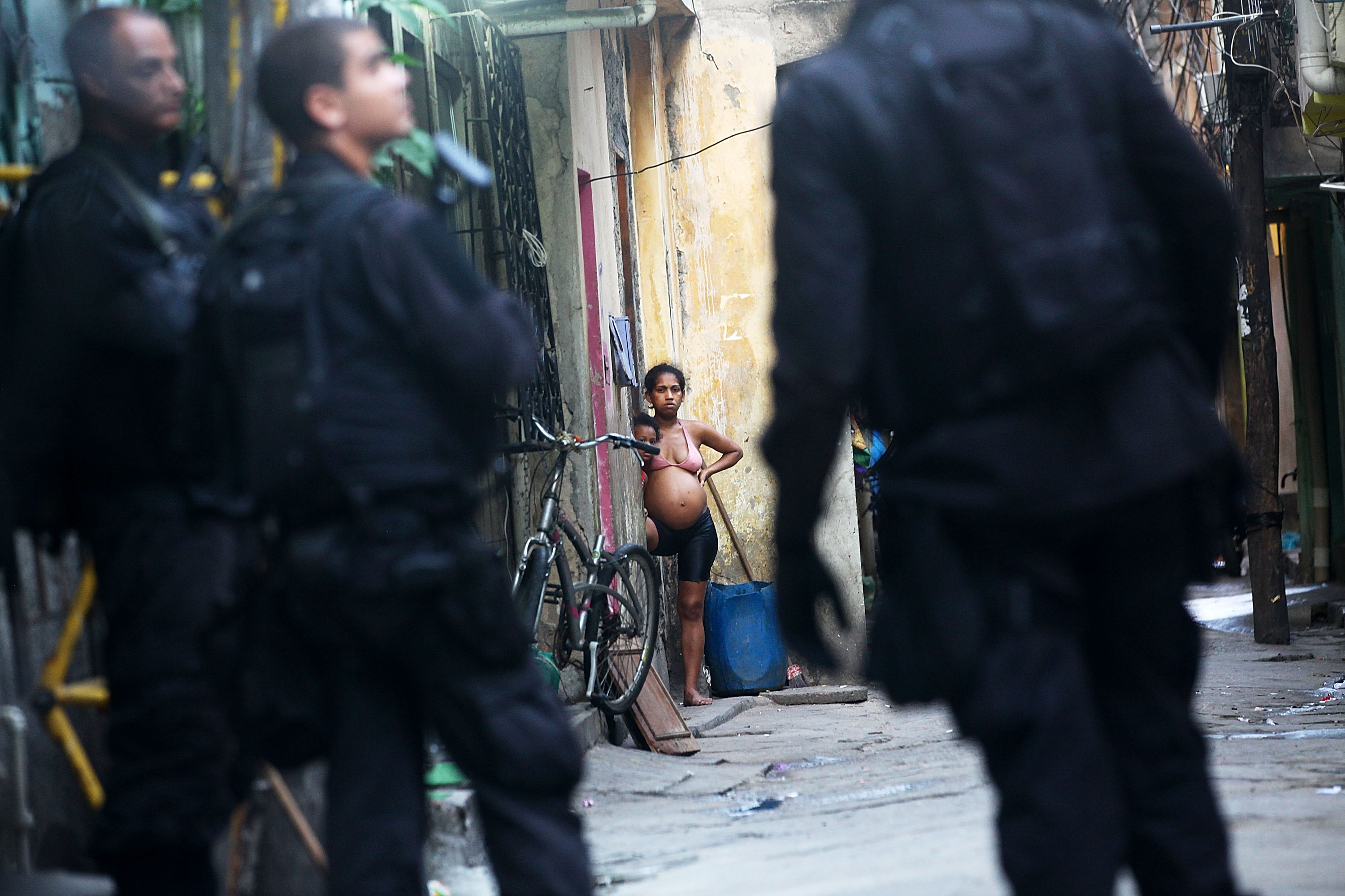 Residents look on as Brazilian military police officers patrol in the unpacified Complexo da Mare, one of the largest favela complexes in Rio, on March 30, 2014 in Rio de Janeiro.
