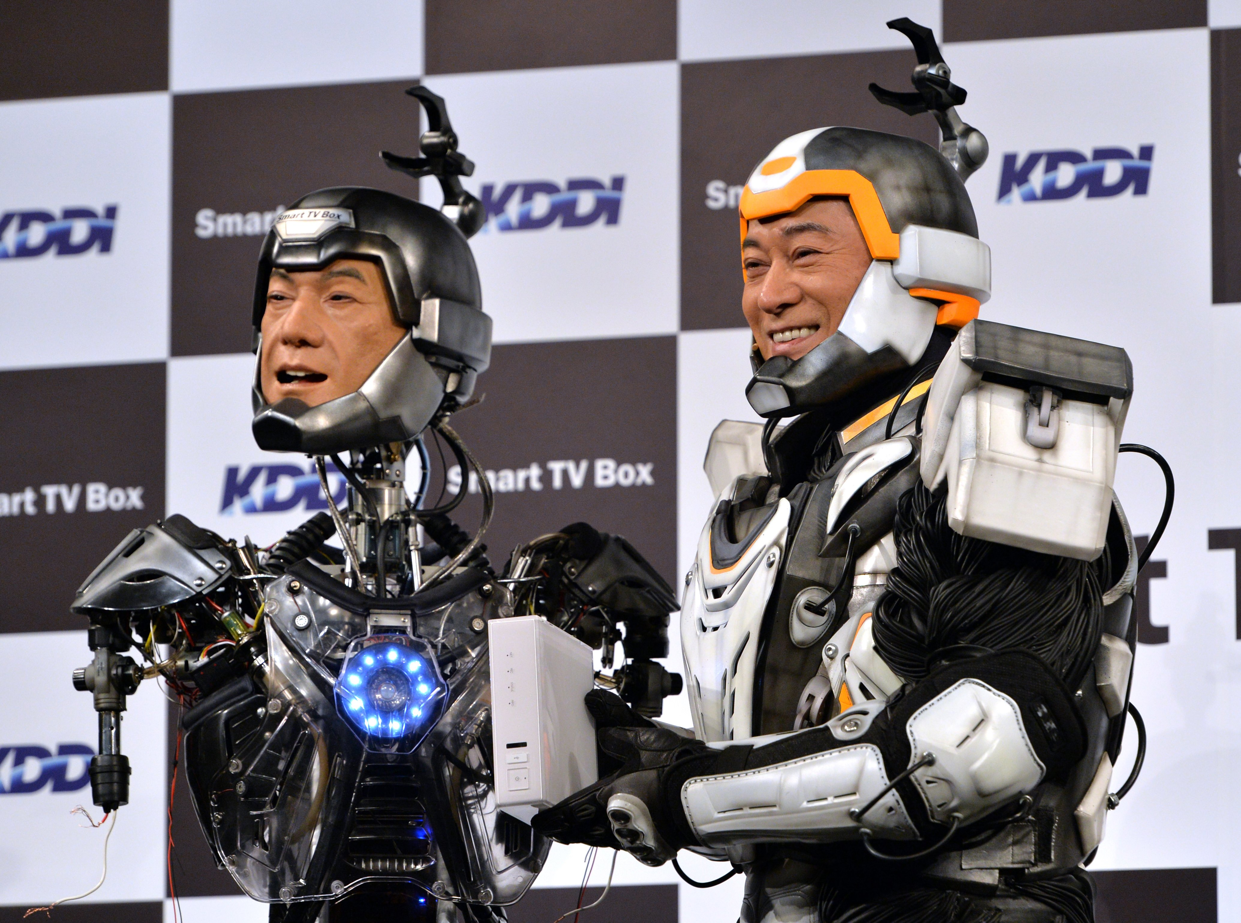 "Japanese actor Ken Matsudaira clad in a robot suit, smiles with an android robot in his likeness called ""Real Android Matsuken"" at a press presentation in Tokyo on November 19, 2013."