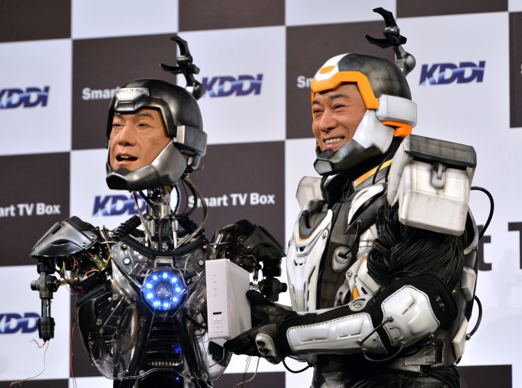 """Japanese actor Ken Matsudaira clad in a robot suit, smiles with an android robot in his likeness called """"Real Android Matsuken"""" at a press presentation in Tokyo on November 19, 2013."""