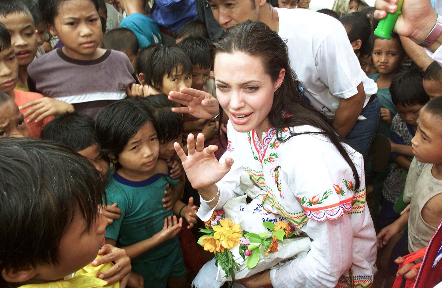 Angelina Jolie receives gifts from the children at the Tham Hin refugee camp on the Thai-Burma border May 19, 2002. Jolie visited the camp on as part of her role as goodwill ambassador for the United Nations High Commissioner for Refugees.