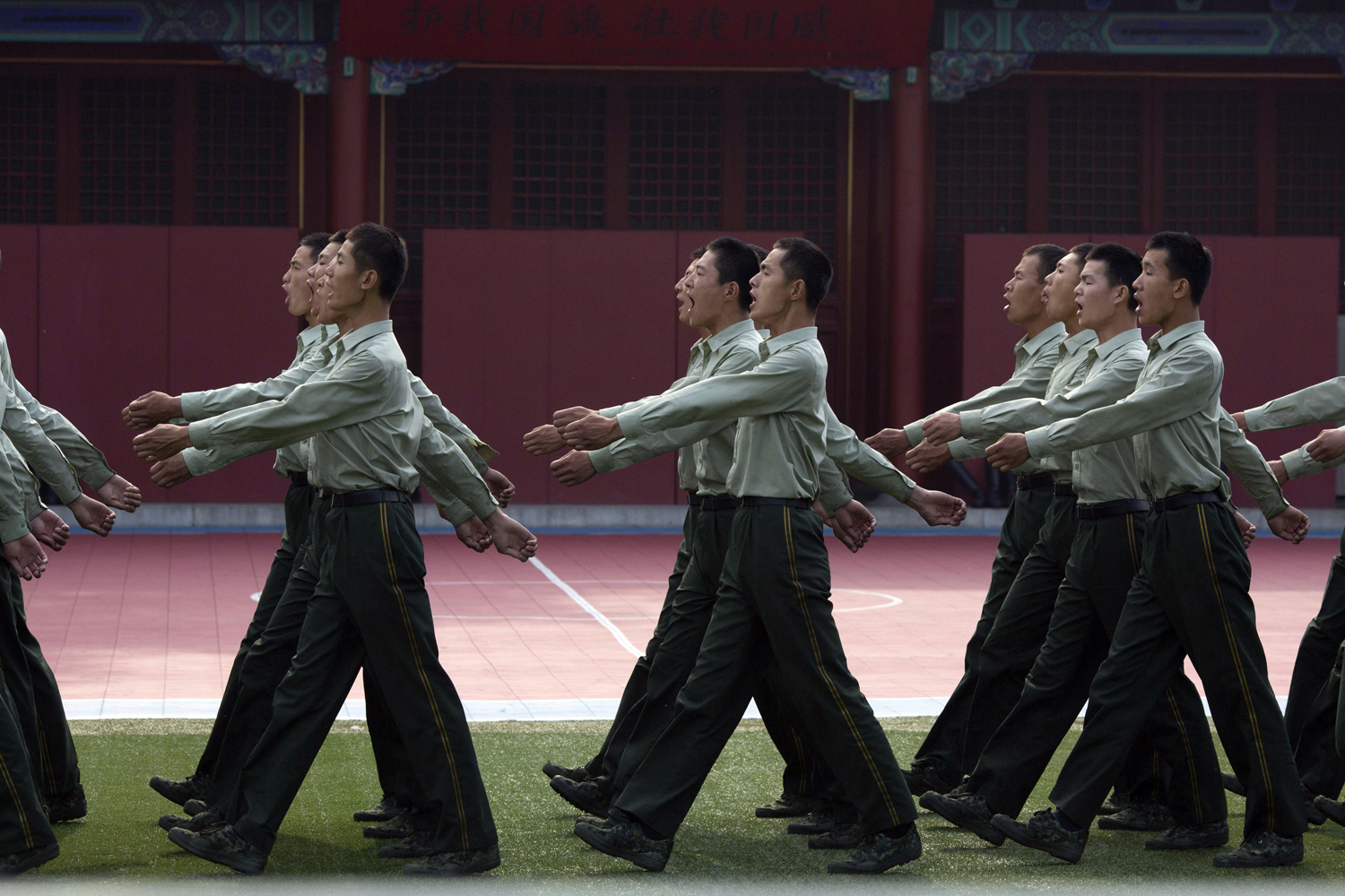 June 4, 2014.  Chinese paramilitary policemen chant slogans as they march at a barrack near Tiananmen Gate in Beijing, China.