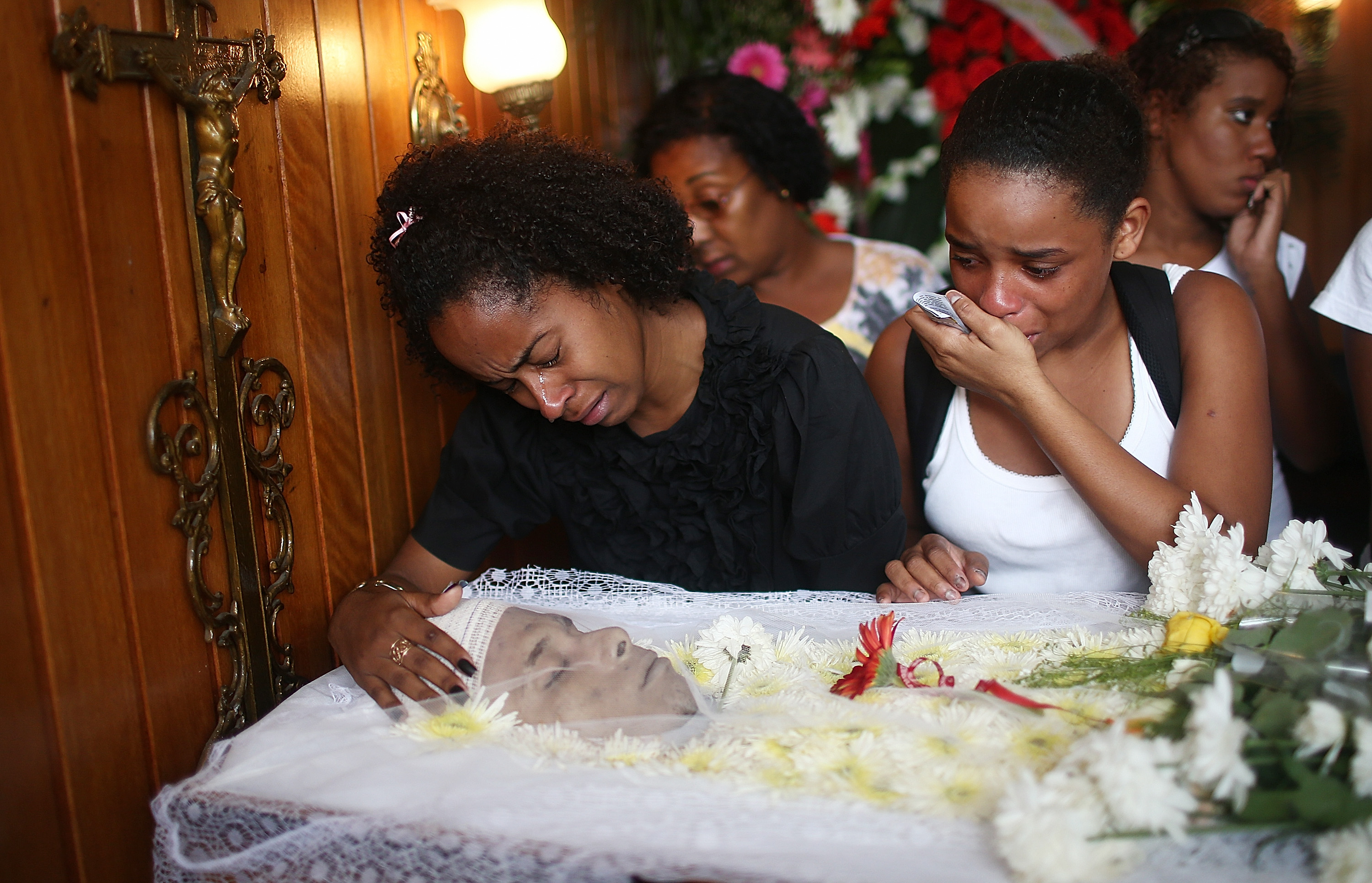 Mourners gather over the body of dancer Douglas Rafael da Silva at his funeral, after he was shot and killed, on April 24, 2014 in Rio de Janeiro.