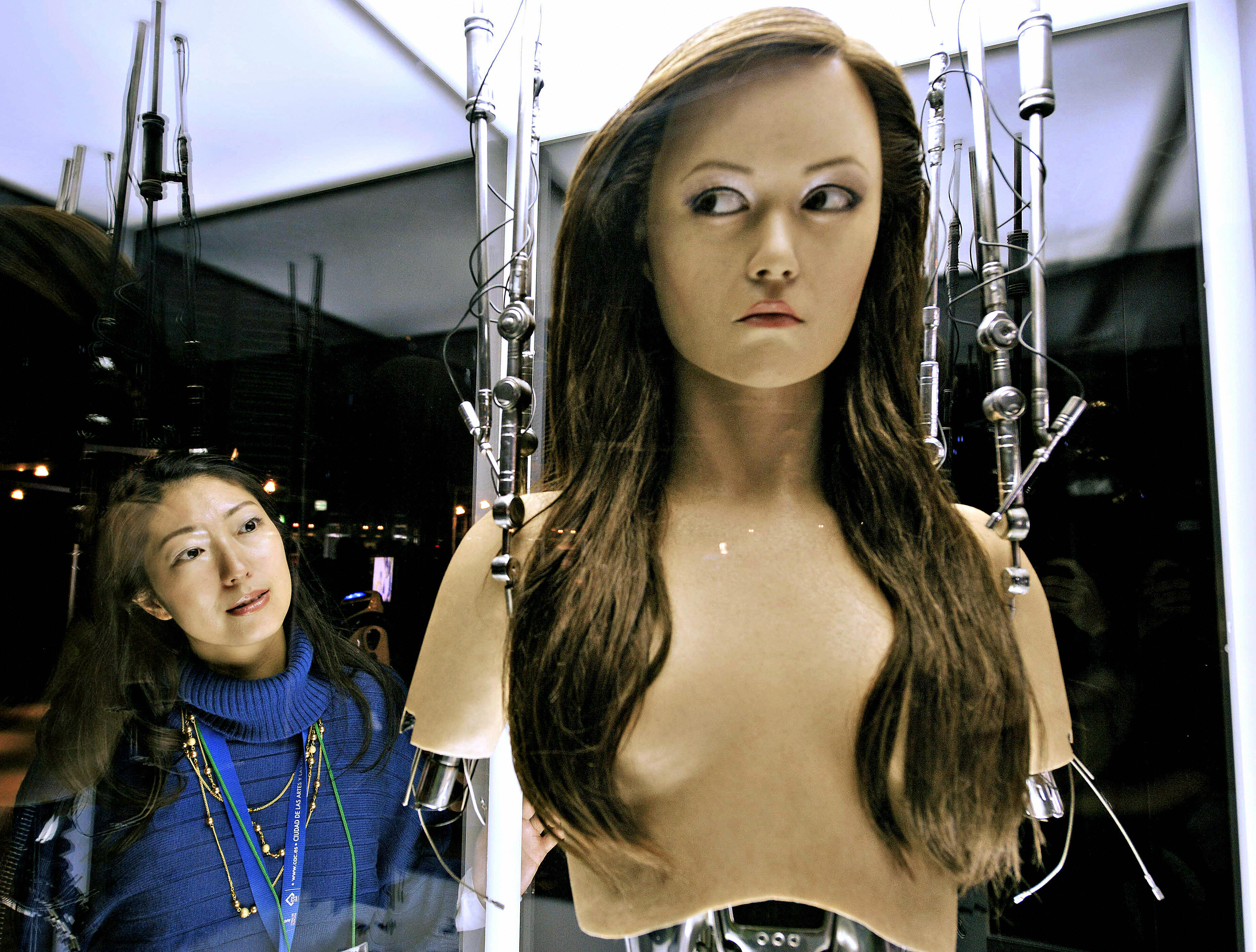 "A woman watches a full-scale figure of a terminator robot ""Cameron Phillipes"" at a preview of the Terminator Exhibition in Tokyo on March 18, 2009."