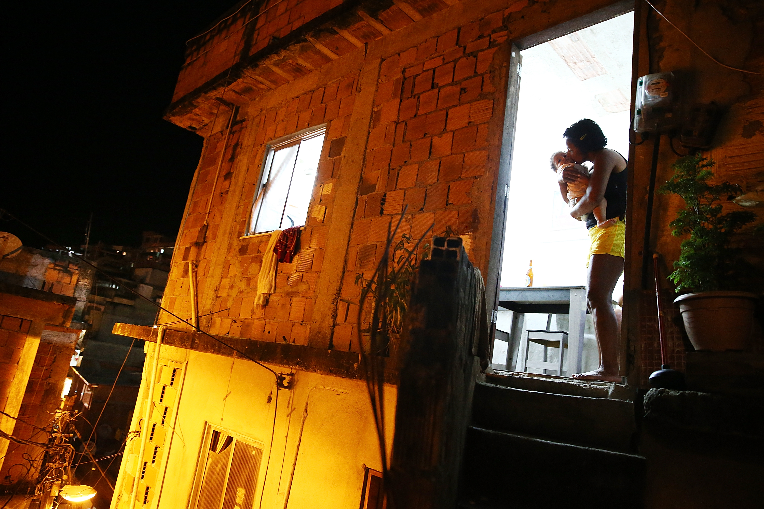 A woman kisses a baby in the Cantagalo shantytown community on March 28, 2014 in Rio de Janeiro.