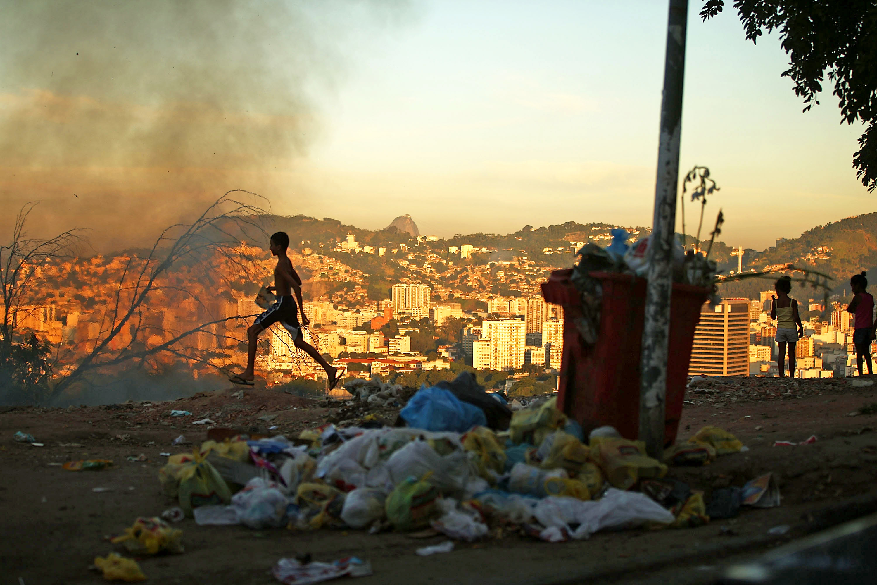 A trash fire burns due to the lack of government assistance of trash disposal in the Mangueira favela, which overlooks the famed Maracana Stadium on June 5, 2014 in Rio de Janeiro.