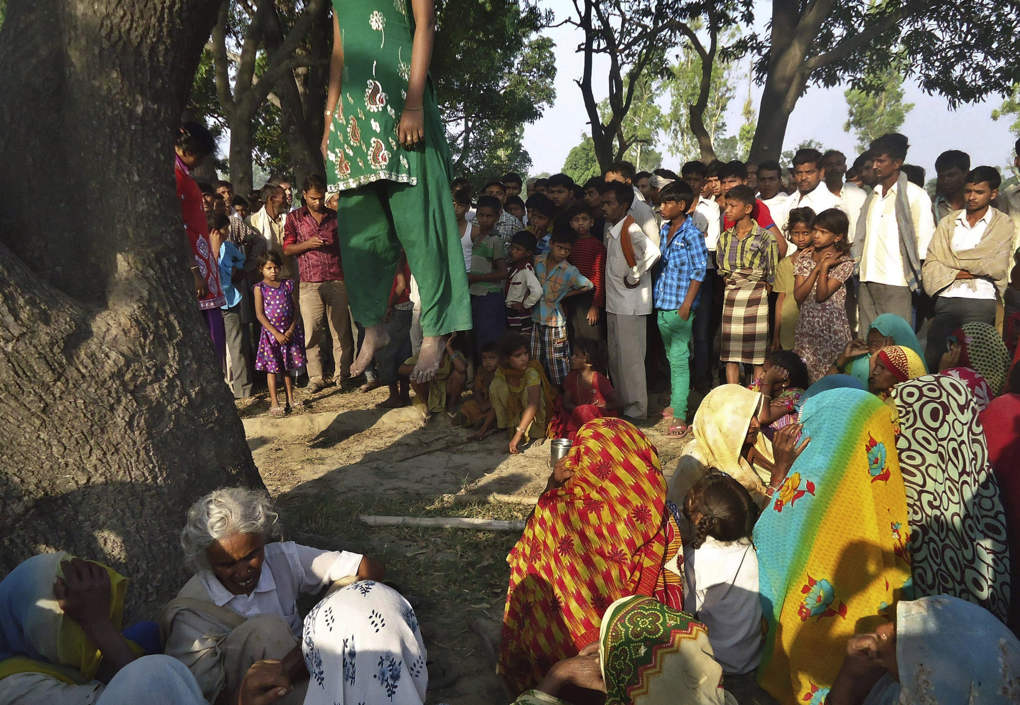 May 28, 2014. Indian villagers gather around the bodies of two teenage sisters hanging from a tree in Katra village in Uttar Pradesh state, India.