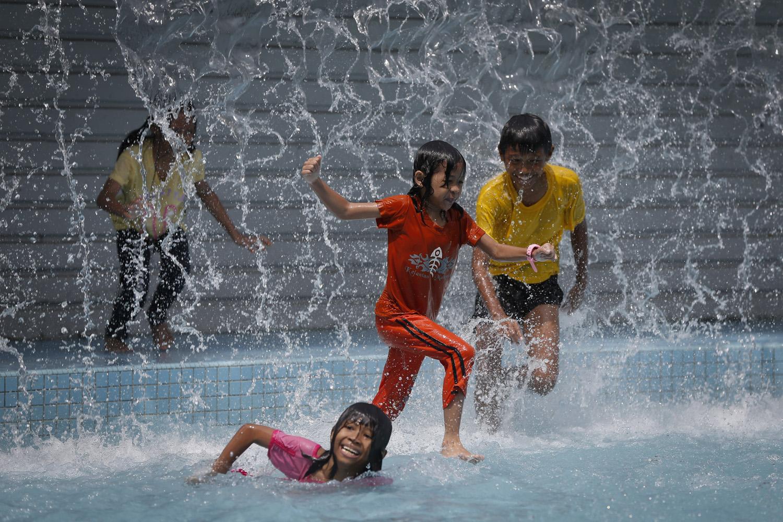 Children play in the pool in front of Malaysia's landmark Petronas Twin Towers in Kuala Lumpur,  June 12, 2014.