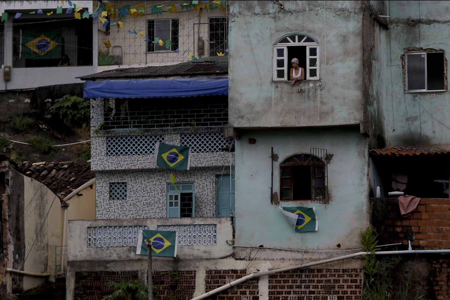 Jun. 12, 2014. A woman stands at a window of a house near the Arena Ponte Nova stadium in Salvador, Brazil.